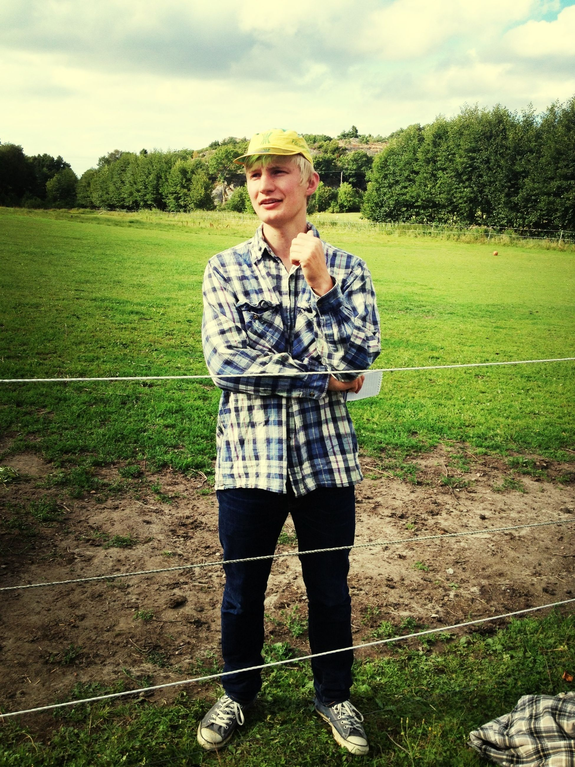 casual clothing, lifestyles, young adult, standing, grass, person, portrait, field, front view, leisure activity, looking at camera, three quarter length, young men, sky, full length, landscape, nature
