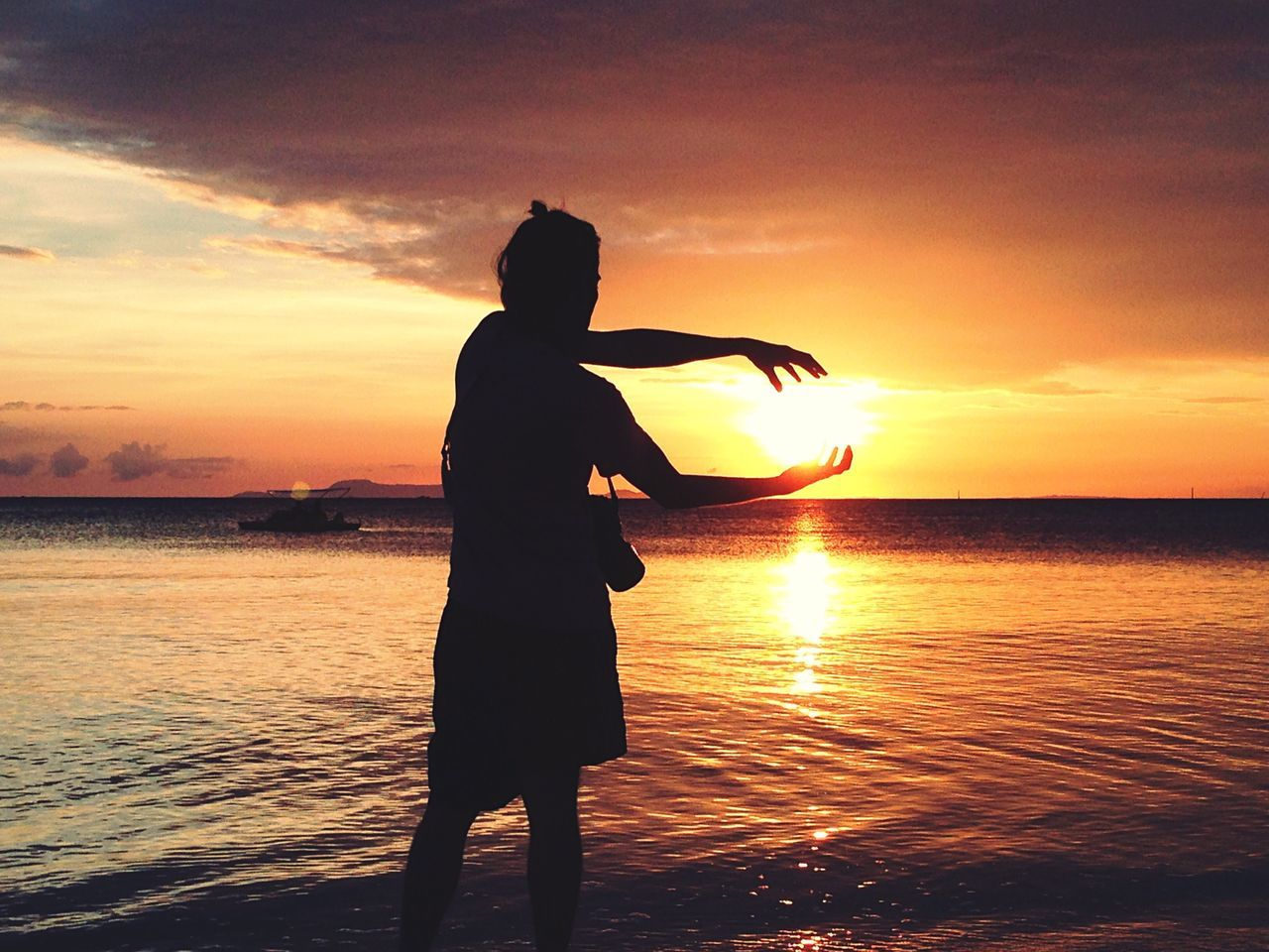 Optical Illusion Of Silhouette Woman Holding Sun At Beach