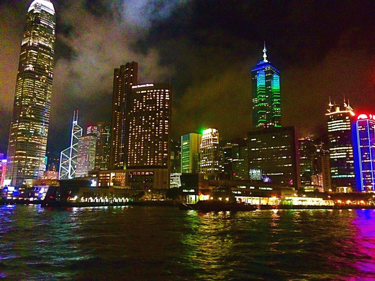 architecture, skyscraper, building exterior, illuminated, tall - high, built structure, night, waterfront, travel destinations, city, tower, cityscape, modern, sky, river, urban skyline, water, outdoors, no people