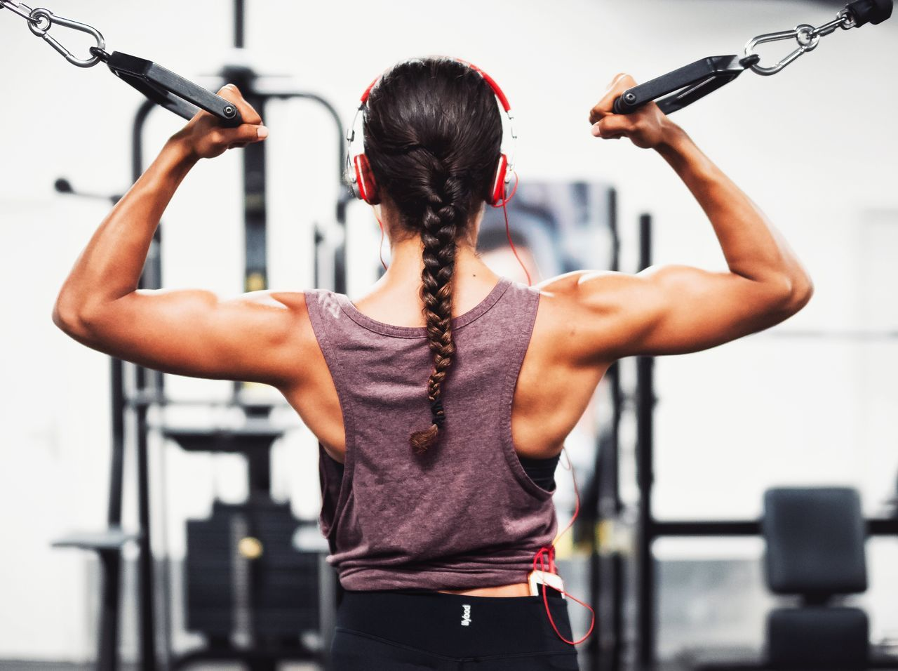 Exercising gym healthy lifestyle strength health club lifestyles muscular build sports training sport Rear view exercise equipment Athlete human muscle Picking Up human body part strength training sports clothing physical activity activity wellbeing Woman fitgirl Curl biceps strong woman
