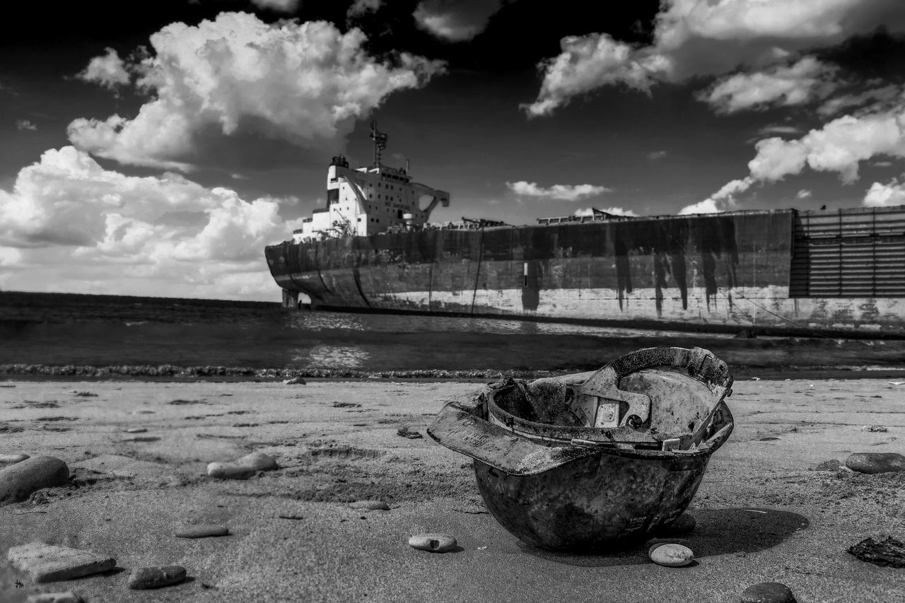 Abandoned Helmet At Beach Against Shipwreck In Sea