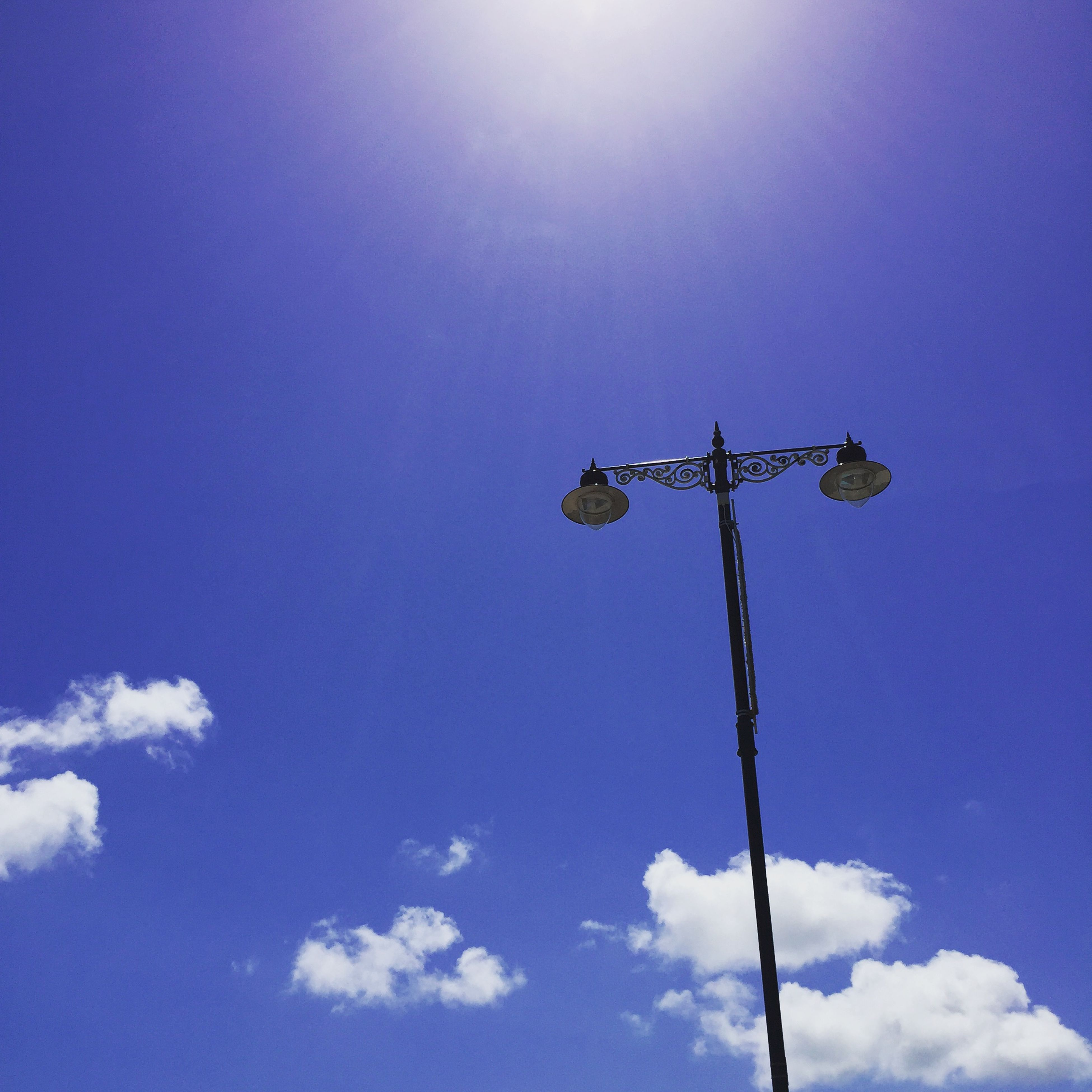 low angle view, blue, street light, sky, lighting equipment, pole, nature, clear sky, copy space, sunlight, day, no people, sun, outdoors, high section, electricity, silhouette, cloud - sky, beauty in nature, electric light