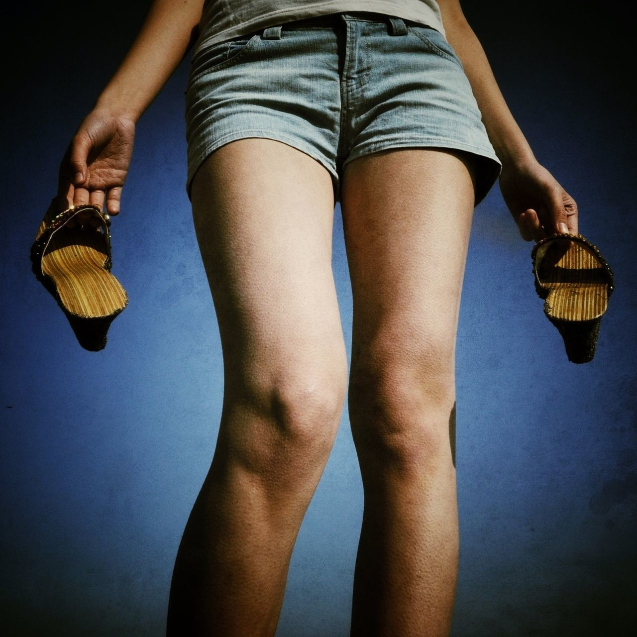 Midsection of woman in hot pants holding heels against blue sky