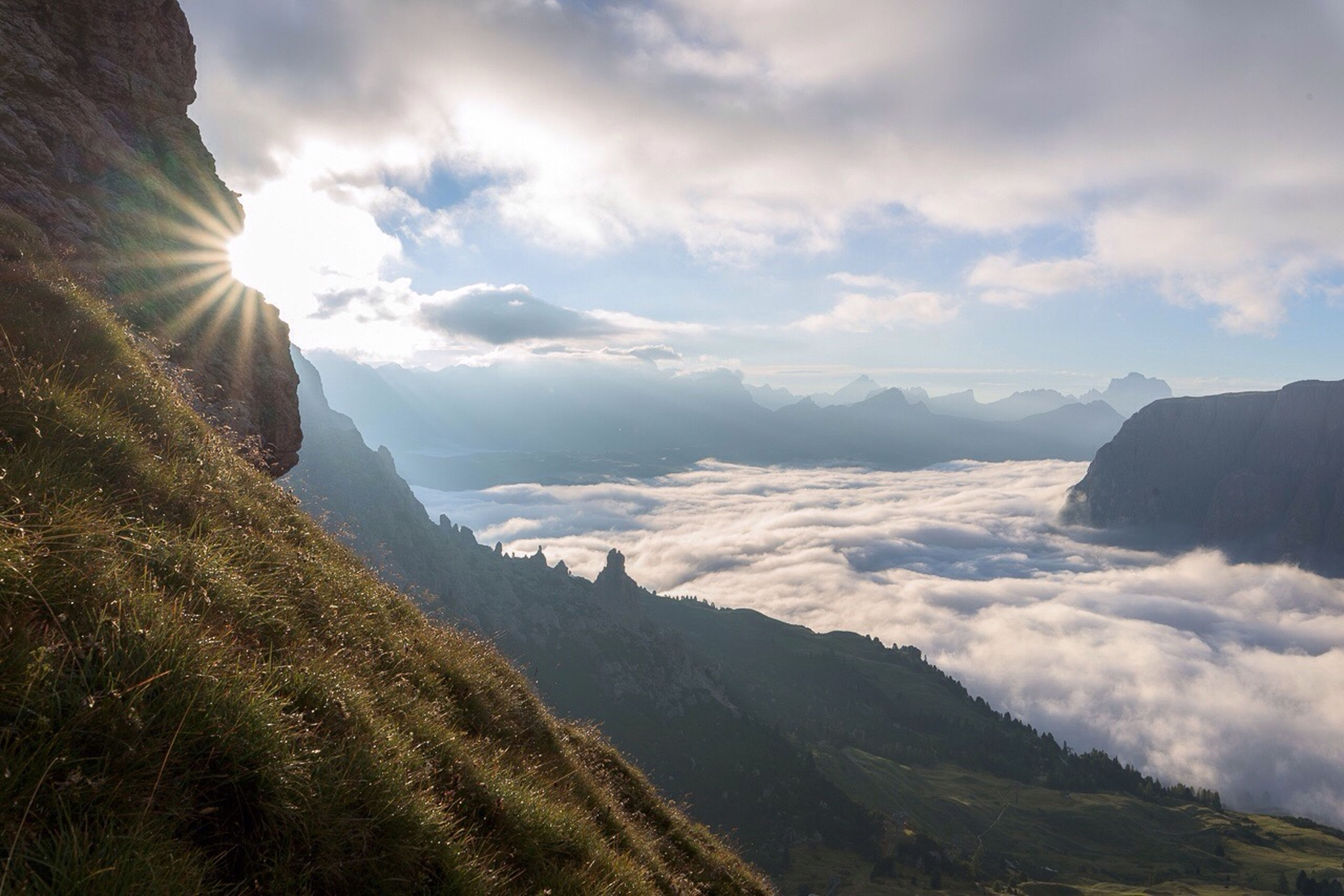 mountain, scenics, tranquil scene, sunbeam, beauty in nature, tranquility, sunlight, landscape, mountain range, lens flare, non-urban scene, idyllic, nature, sun, cloud - sky, majestic, sky, mountain peak, remote, valley, cloud, tourism, day, sunny, aerial view, outdoors, cloudscape, physical geography, high up, bright, countryside, solitude