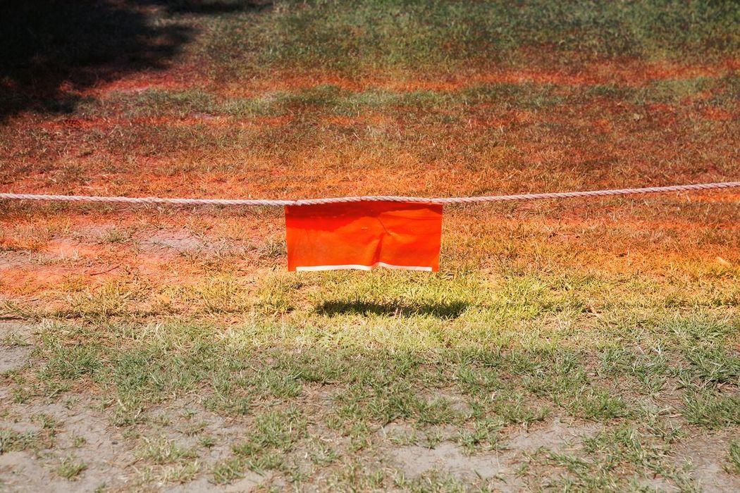 Rotes Tuch an Absperrungsseil vor einem Rasen Absperrung Durchgang Verboten Gesperrt Gesperrter Rasen Kein Durchgang Rasen Red Rot Roter Rasen Rotes Tuch Seil Stop Sign Stopp
