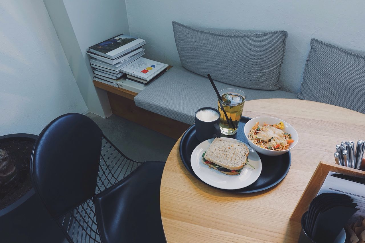 table, indoors, food and drink, home interior, sofa, high angle view, drink, chair, plate, food, drinking glass, refreshment, breakfast, no people, day, technology, healthy eating, freshness