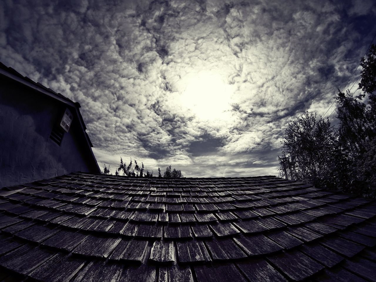 Low angle view of house roof against cloudy sky