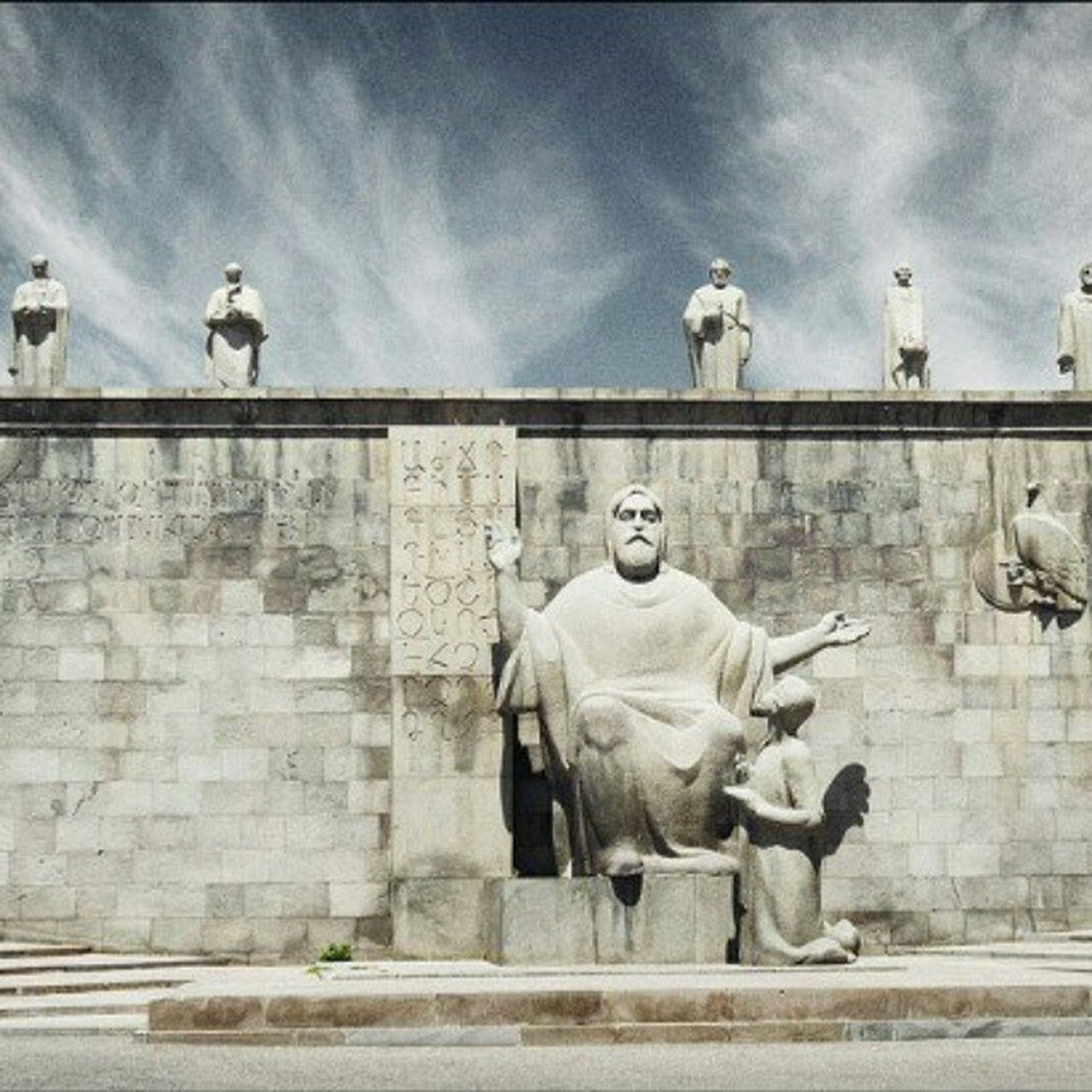 statue, human representation, sculpture, art and craft, art, architecture, building exterior, built structure, creativity, sky, low angle view, animal representation, cloud - sky, day, wall - building feature, outdoors, history, cloud