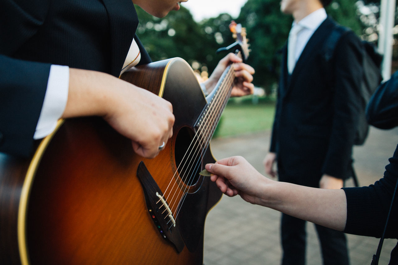 music, musical instrument, playing, real people, midsection, two people, focus on foreground, togetherness, skill, guitar, arts culture and entertainment, men, performance, outdoors, day, human hand, musician, people