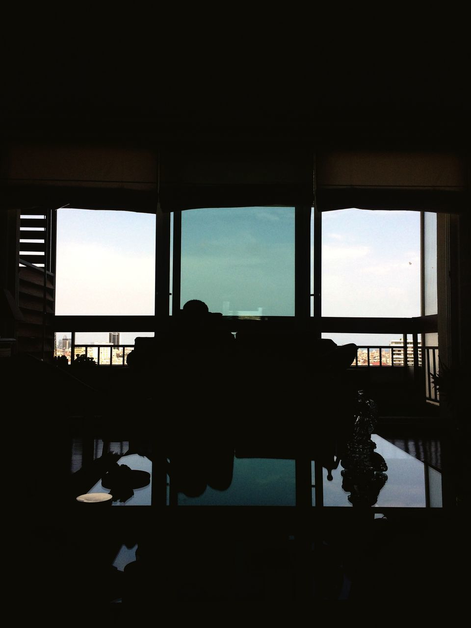 window, silhouette, indoors, sky, table, day, real people, built structure, looking through window, men, architecture, sitting, sea, one person, nature, airplane, water, people