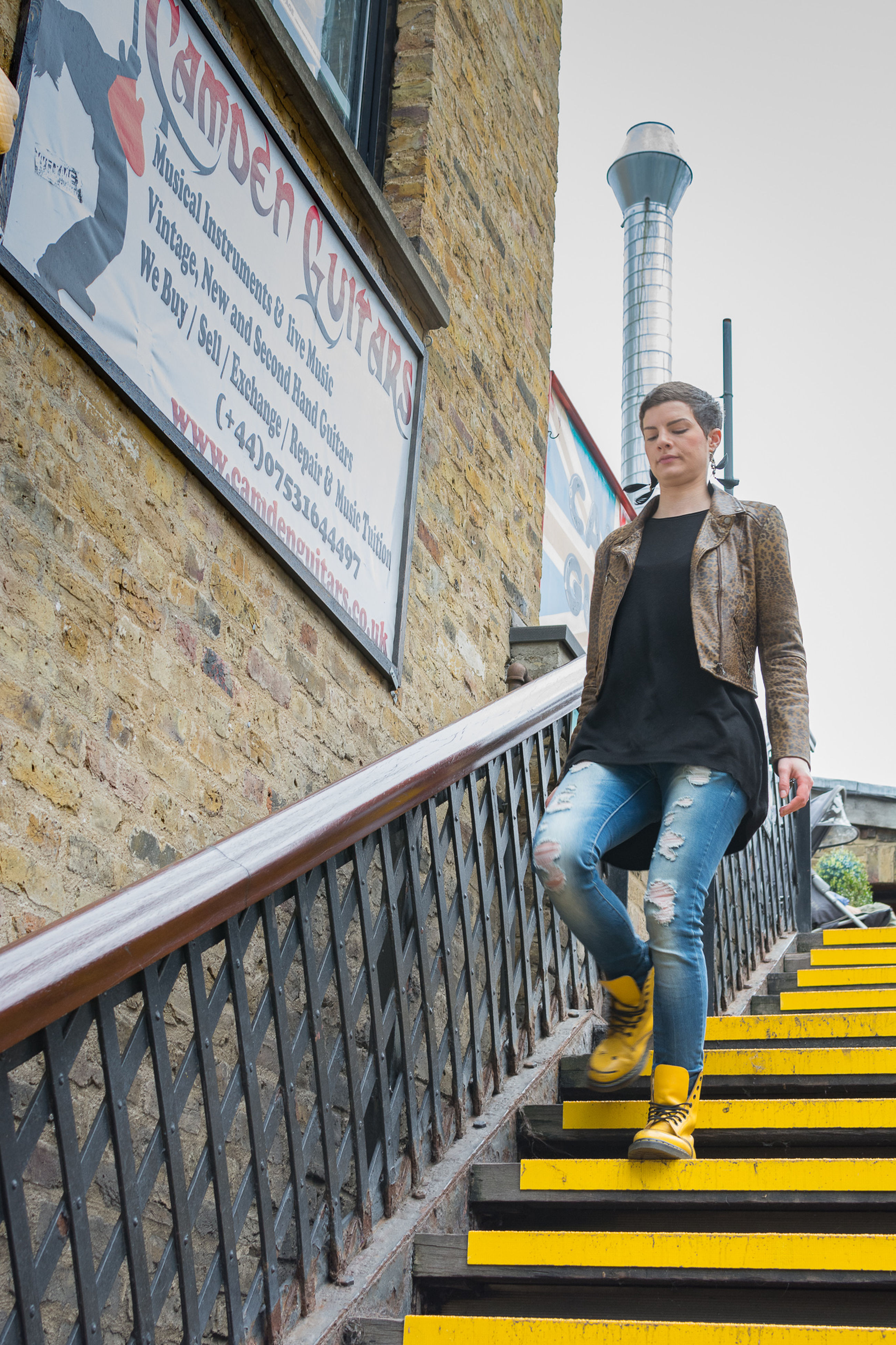 lifestyles, full length, railing, built structure, casual clothing, architecture, standing, building exterior, steps, young adult, leisure activity, communication, person, text, three quarter length, front view, day, young men