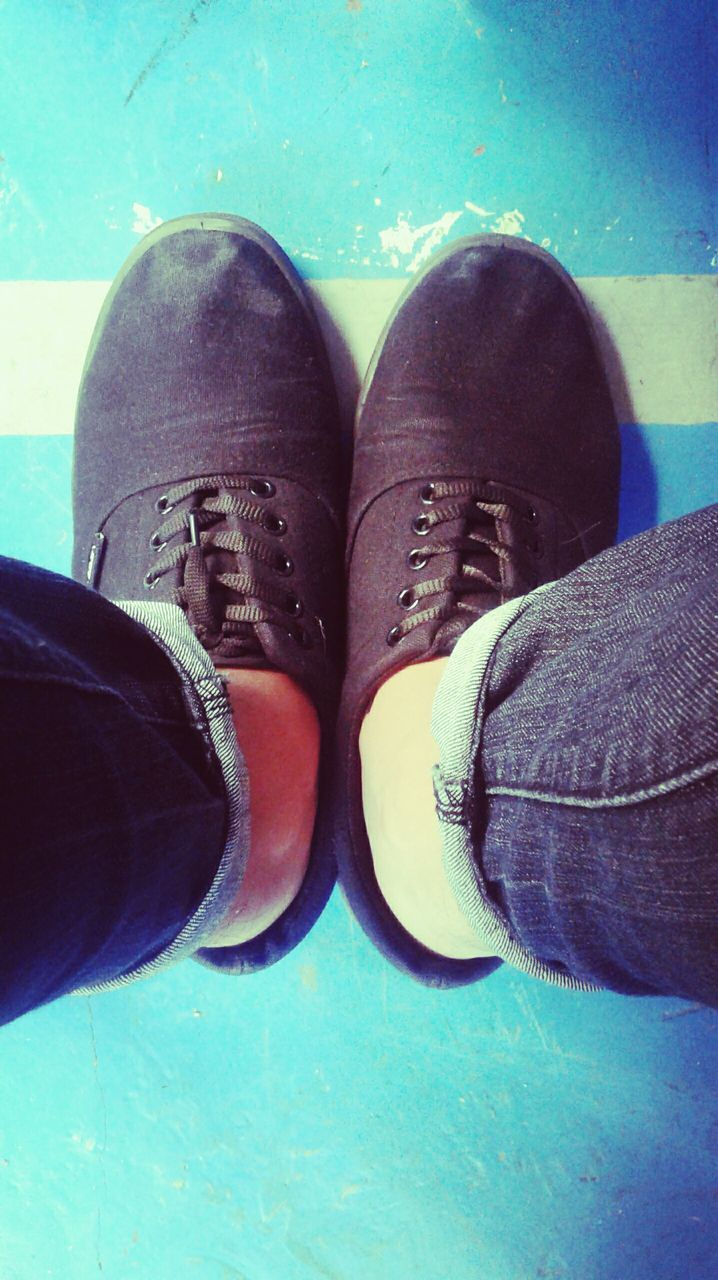 shoe, low section, personal perspective, human leg, human body part, jeans, one person, real people, human foot, high angle view, lifestyles, standing, men, pair, directly above, fashion, canvas shoe, day, leisure activity, blue, close-up, indoors, people