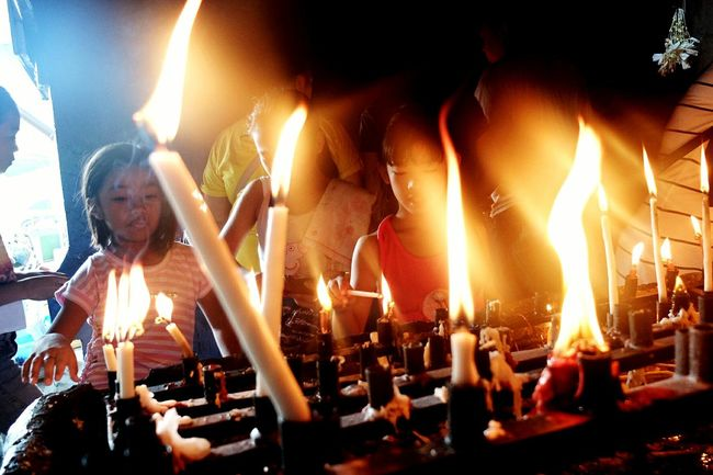 Flame Religion Spirituality Arts Culture And Entertainment Indoors  Illuminated Horizontal People Night Burning Adult Young Adult Person Faith Faith&devotion Candles Candlelight Candle Candle Light Religious  Heat - Temperature Burning Flame Tradition Fire - Natural Phenomenon