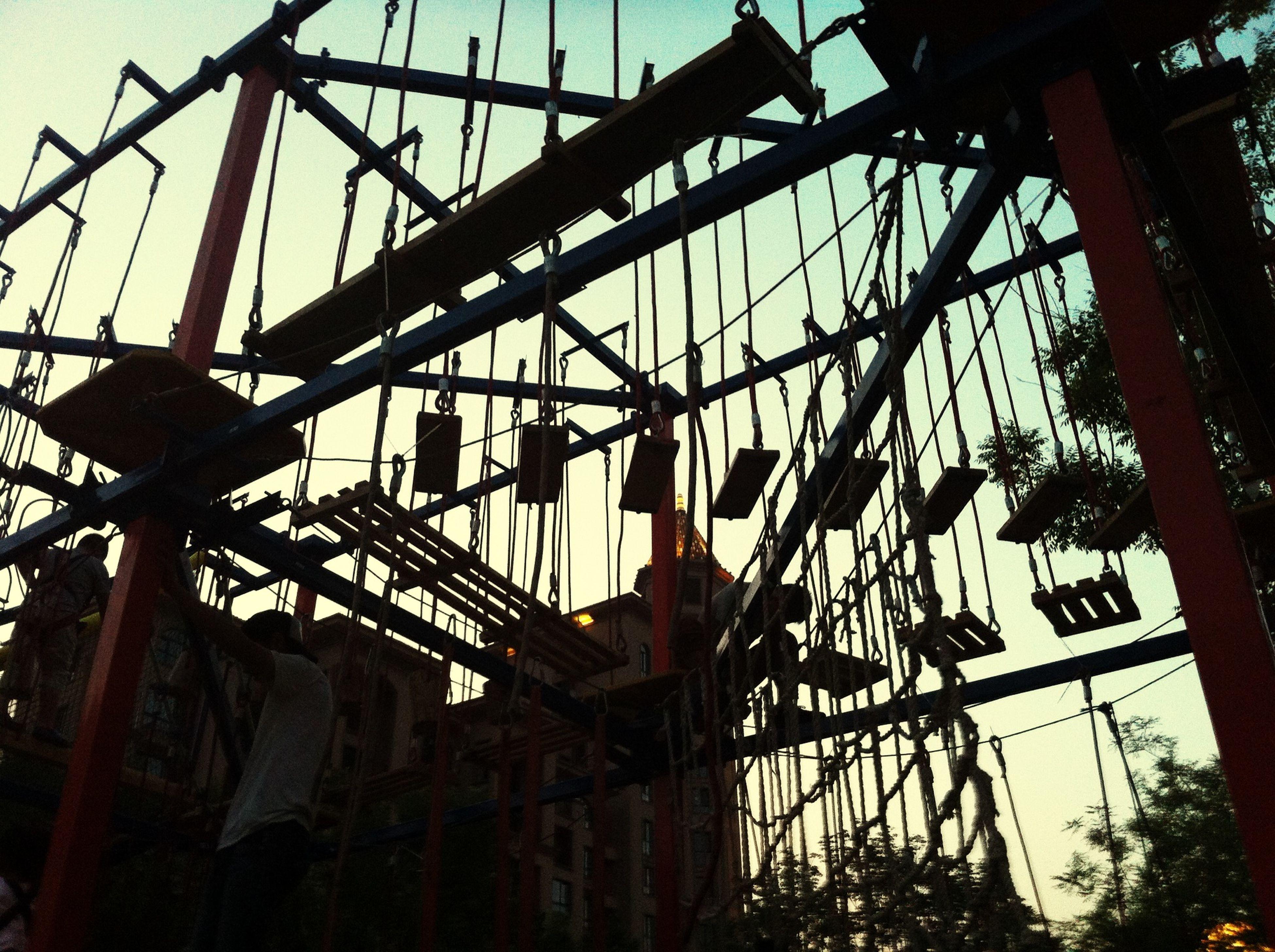 low angle view, metal, silhouette, sky, clear sky, metallic, built structure, amusement park, amusement park ride, architecture, connection, arts culture and entertainment, dusk, transportation, no people, sunset, outdoors, ferris wheel, day, electricity pylon