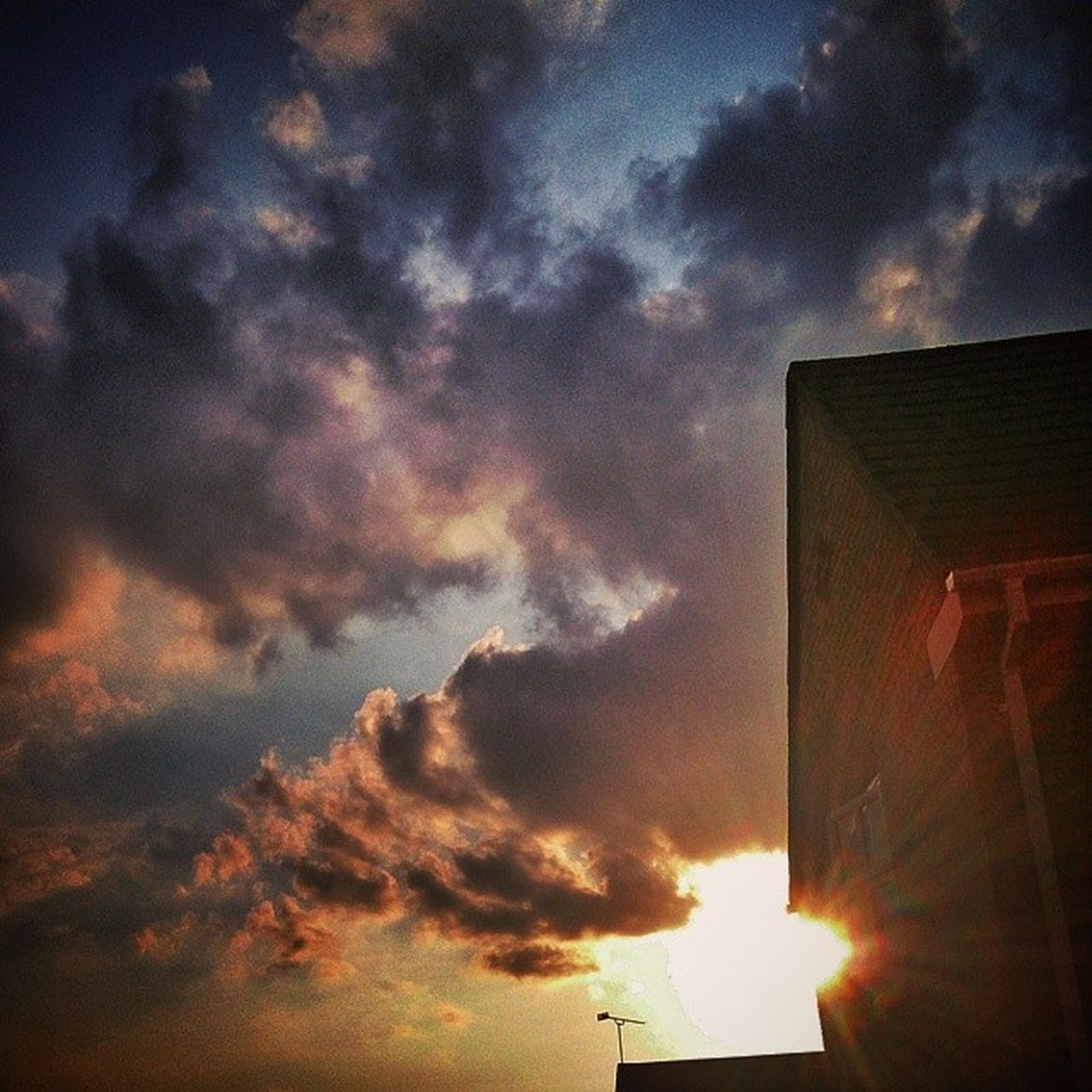 sky, low angle view, building exterior, cloud - sky, architecture, built structure, sunset, cloudy, cloud, silhouette, sun, sunbeam, building, sunlight, dramatic sky, outdoors, weather, street light, nature, no people