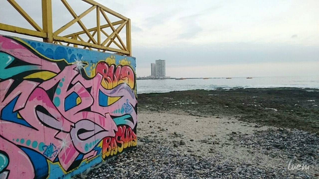 sea, beach, graffiti, horizon over water, multi colored, built structure, sky, outdoors, water, architecture, no people, day, nature, building exterior, scenics, beauty in nature