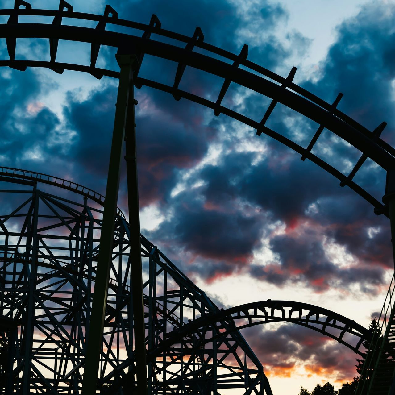 Low Angle View Of Rollercoaster Against Cloudy Sky At Sunset