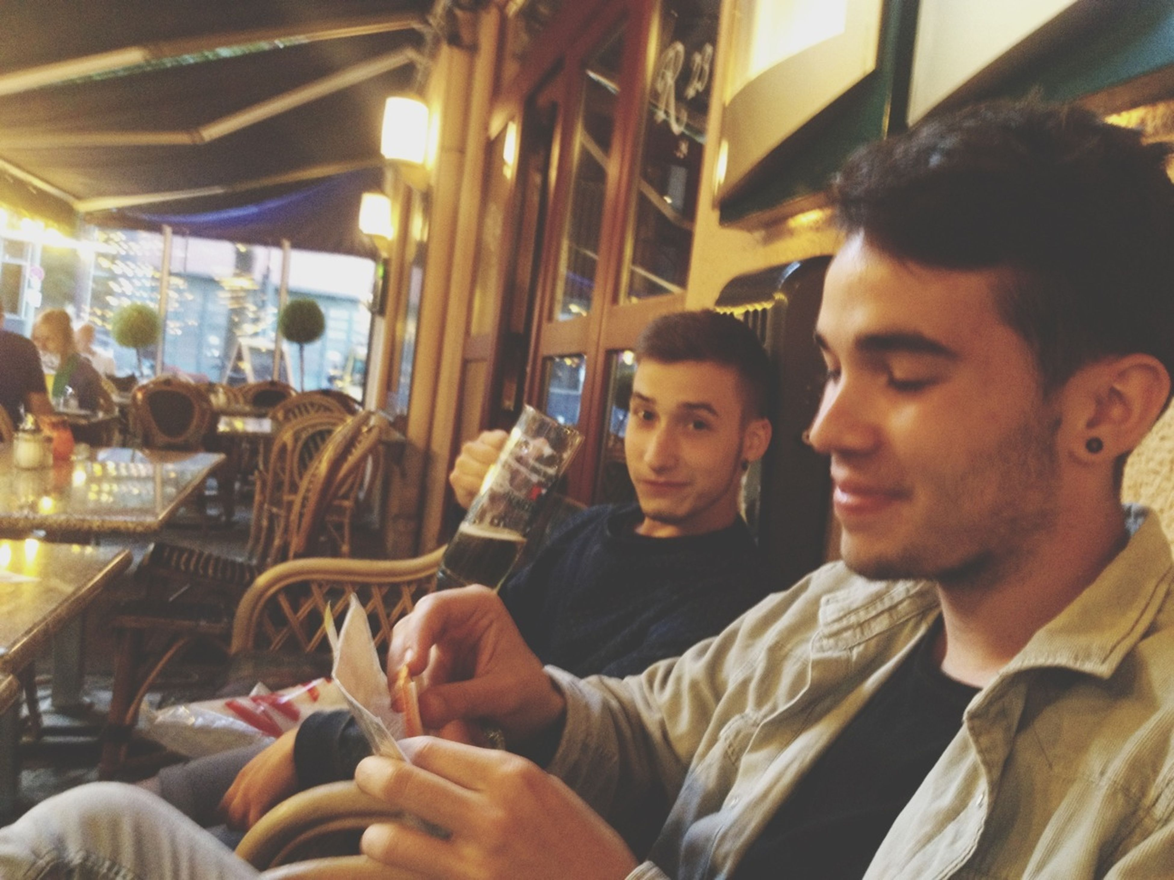 indoors, lifestyles, person, leisure activity, young adult, sitting, casual clothing, young men, togetherness, headshot, portrait, restaurant, smiling, looking at camera, wireless technology, waist up
