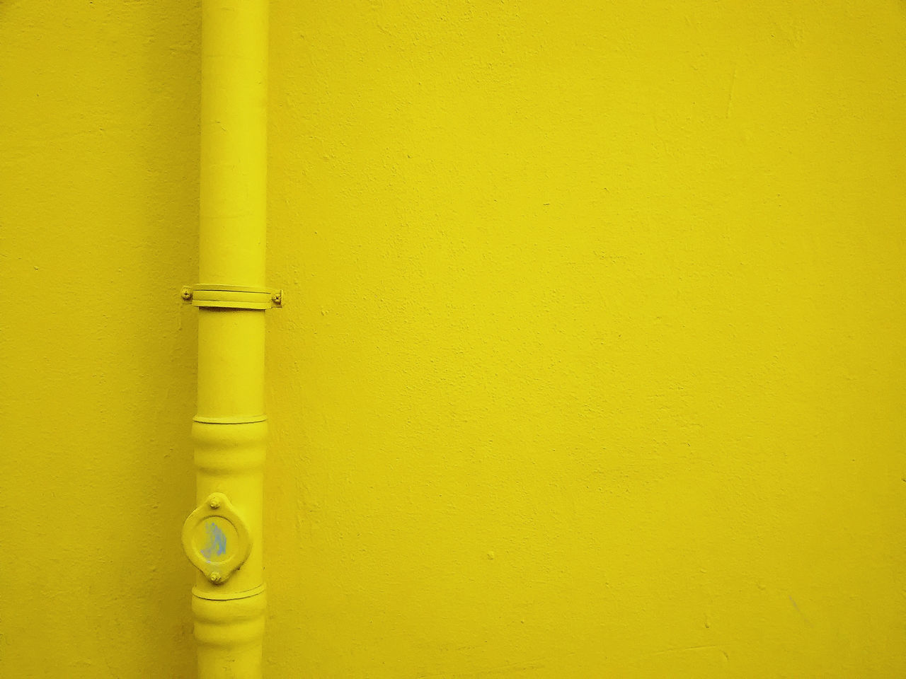 Close-Up Of Pipe Against Yellow Wall