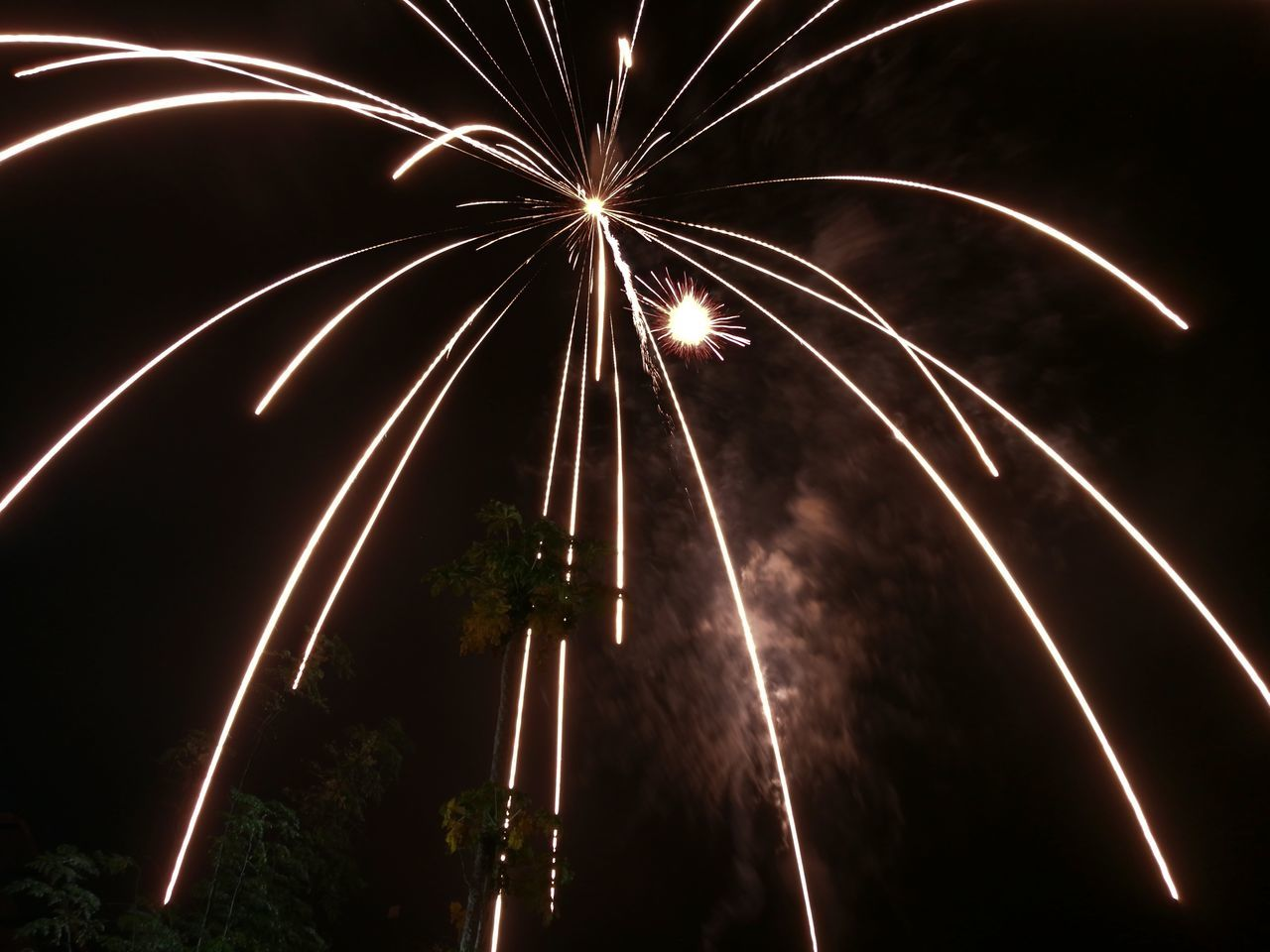 motion, long exposure, night, firework display, firework - man made object, illuminated, blurred motion, exploding, celebration, glowing, arts culture and entertainment, low angle view, outdoors, event, firework, no people, sky