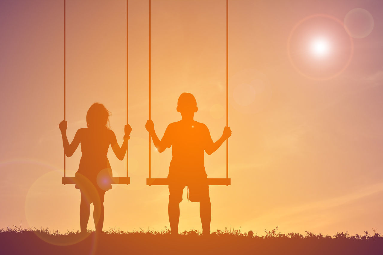 Children Playing On Swing Against Sky During Sunset