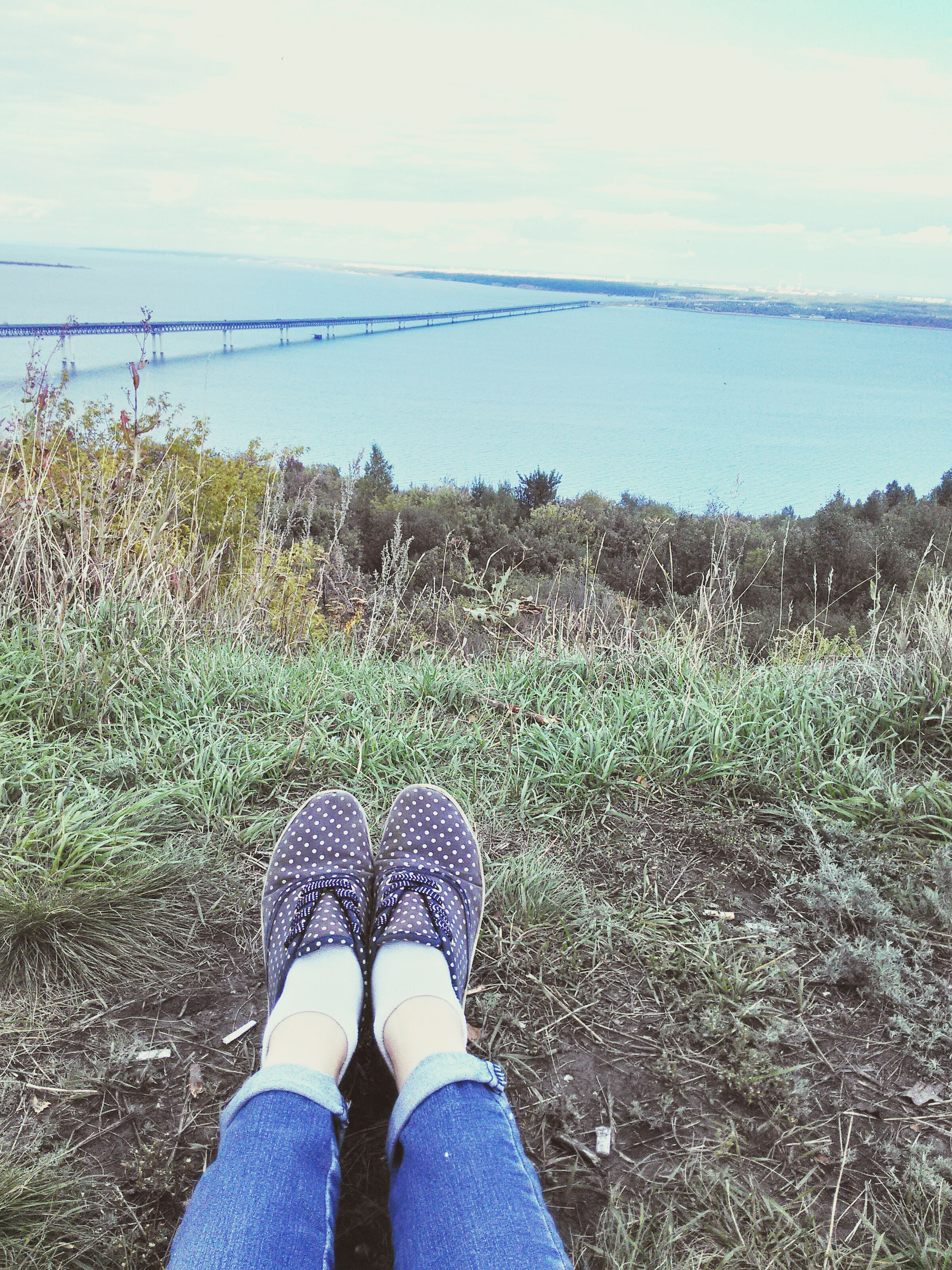 low section, person, personal perspective, standing, water, sky, shoe, lifestyles, leisure activity, tranquility, nature, tranquil scene, grass, men, beauty in nature, scenics, human foot