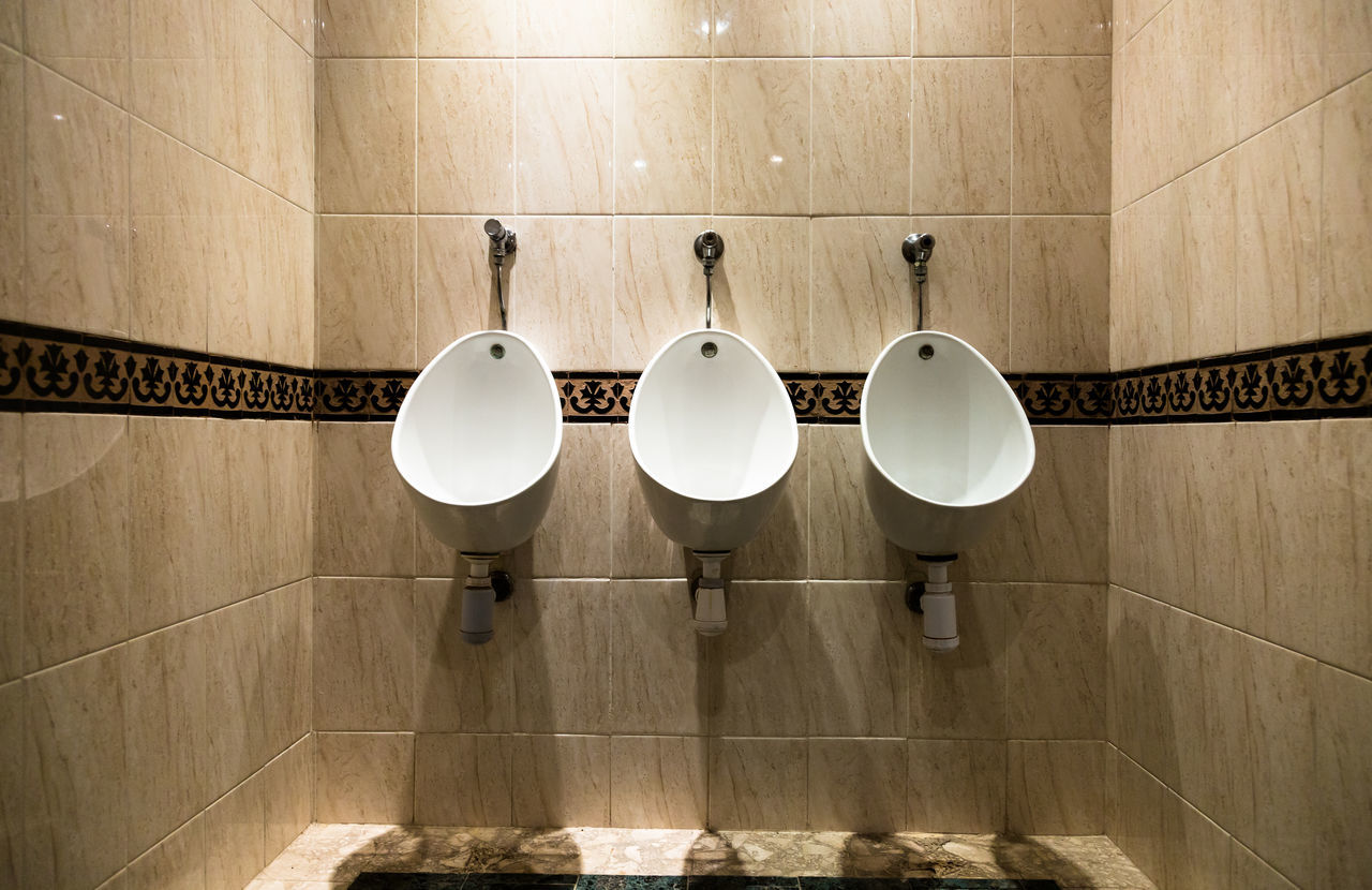 Bathroom Bright White Clear Sky Comfort Convenience Domestic Bathroom Domestic Room Hotel Hygiene In Row Indoors  Man Modern No People Open Space Public Rest Room Stone Tile Tiled Floor Toilet Toilet Bowl Triple Urinals Wash Hands