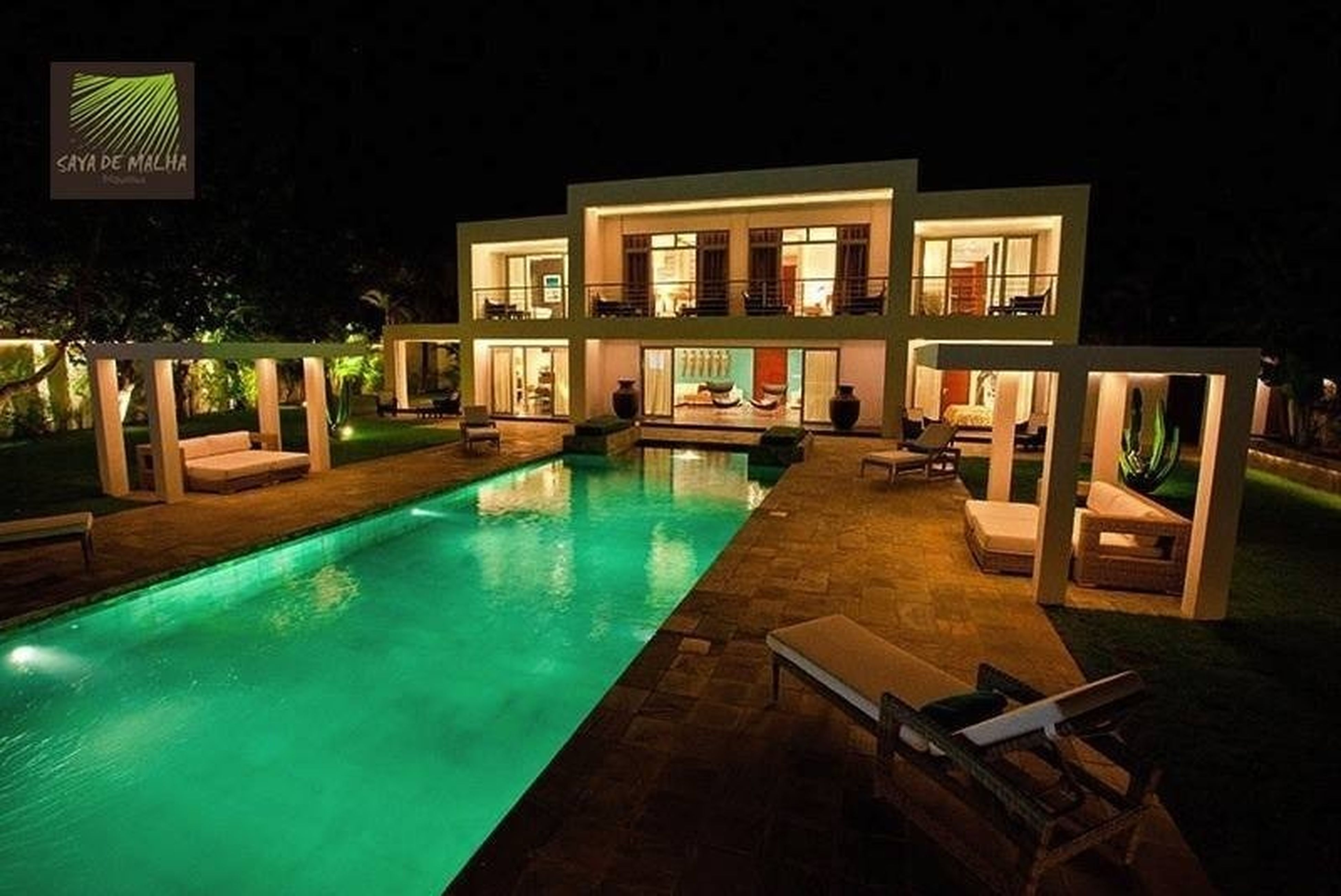 architecture, built structure, building exterior, water, reflection, house, night, window, residential building, illuminated, swimming pool, table, residential structure, building, city, tree, absence, no people, outdoors, chair