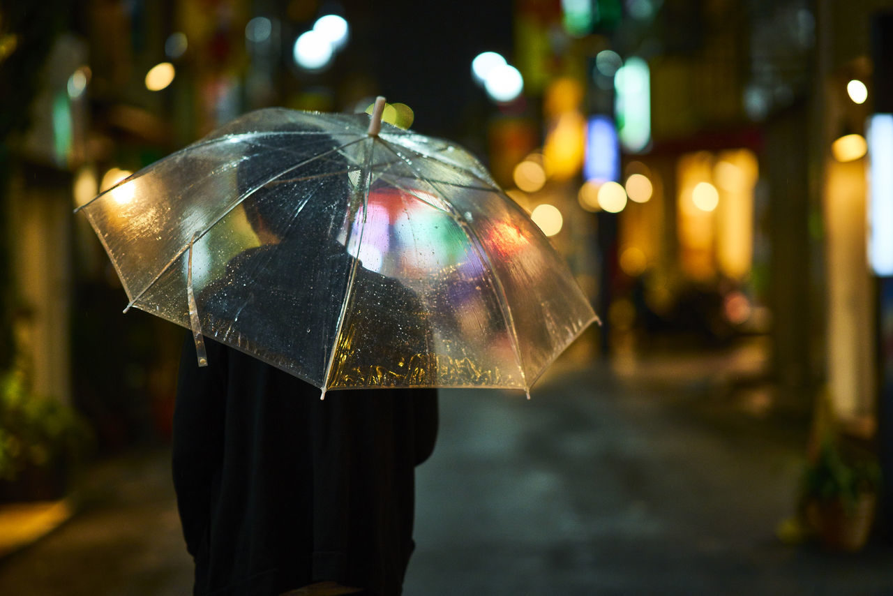 umbrella, rain, protection, rainy season, night, wet, illuminated, focus on foreground, weather, raindrop, street, city, outdoors, shelter, close-up, under, men, water, one person, people