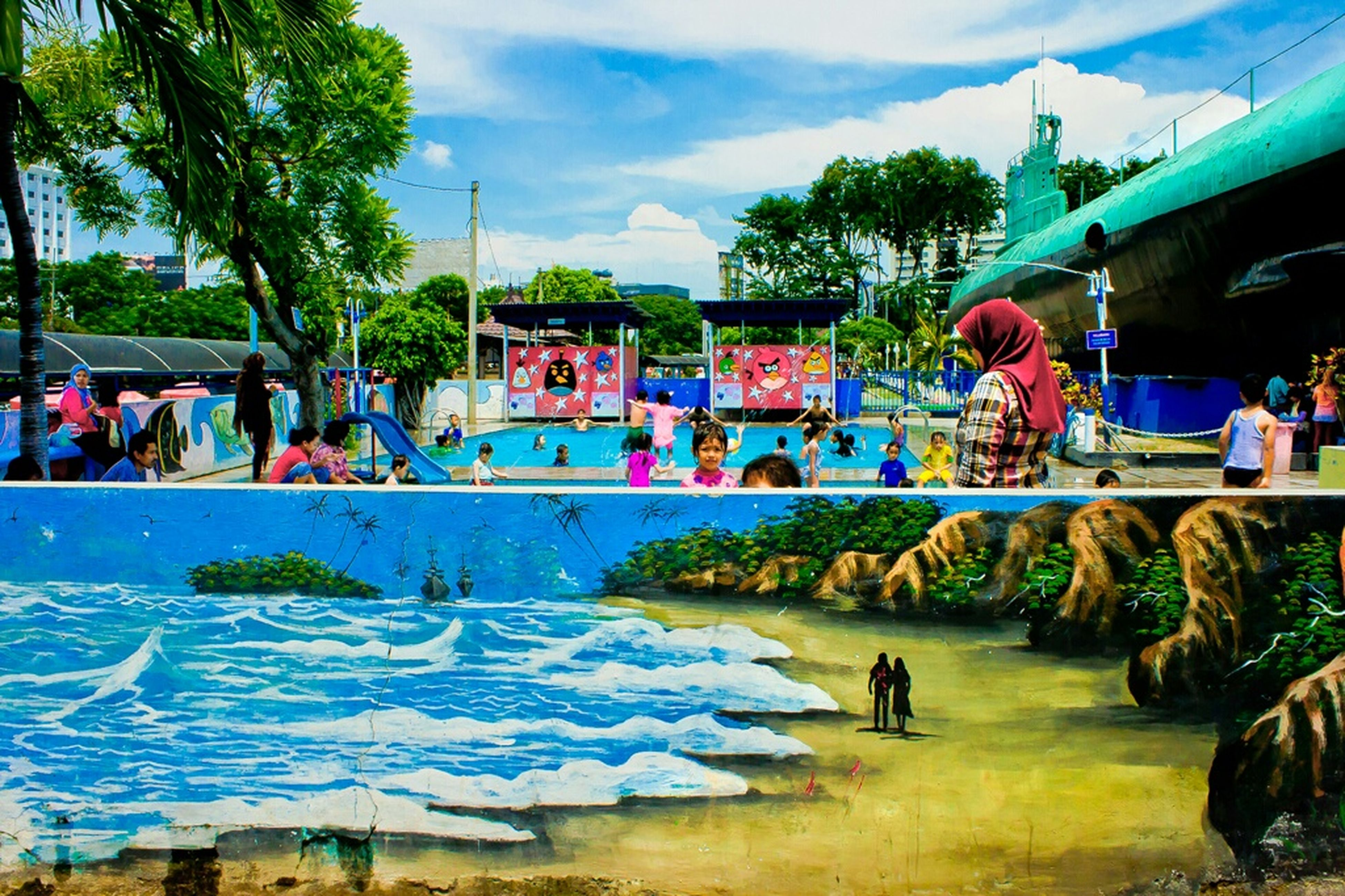 water, lifestyles, sky, leisure activity, built structure, architecture, large group of people, men, cloud - sky, person, building exterior, tree, swimming pool, fountain, tourist, enjoyment, travel, cloud, incidental people