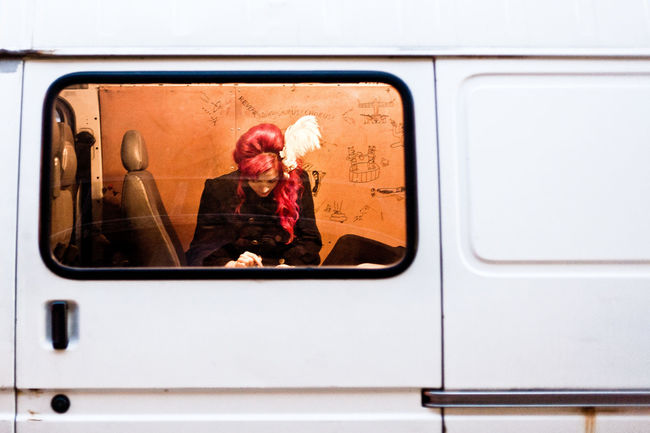 Woman in a white van parked near Brick Lane in London, UK Adults Only Commuter Day Elegant Woman Feather  Hair Piece Journey London London Lifestyle Mobile Phone Mode Of Transport One Person Outdoors Passenger Public Transportation Real People Street Photography Streetphoto Streetphotography Through The Window Transportation Vehicle Interior Window Young Adult Young Women