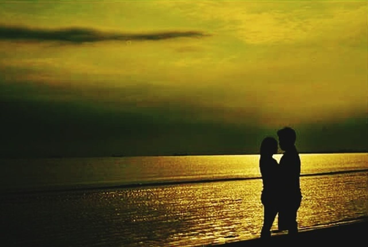 two people, sea, silhouette, sunset, water, real people, togetherness, horizon over water, scenics, love, standing, beauty in nature, tranquil scene, nature, leisure activity, outdoors, sky, beach, men, tranquility, lifestyles, bonding, women, vacations, full length, day, adult, people