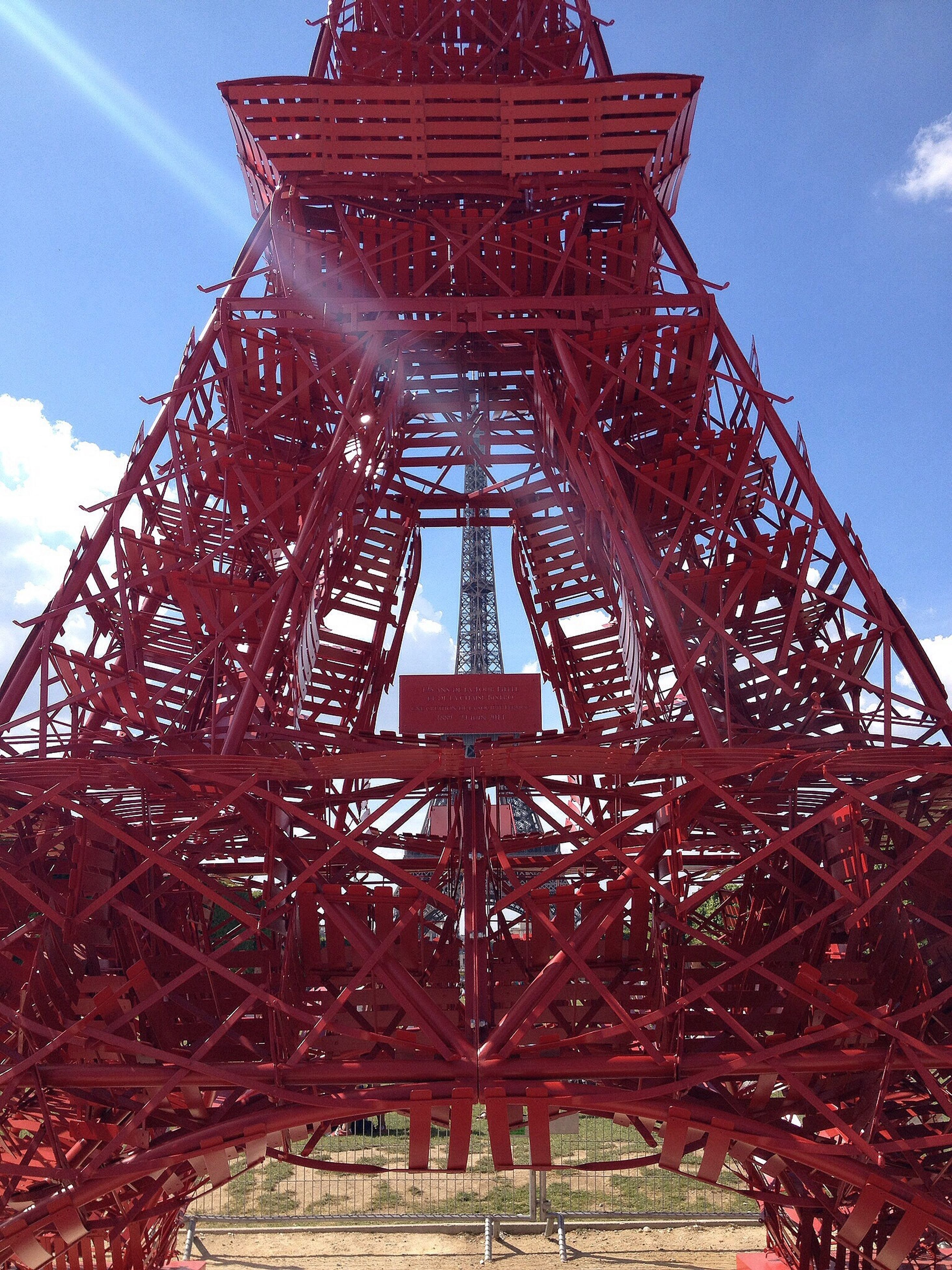 built structure, low angle view, metal, architecture, red, sky, metallic, blue, tower, building exterior, day, outdoors, communication, no people, sunlight, travel destinations, famous place, cloud, cloud - sky, tree