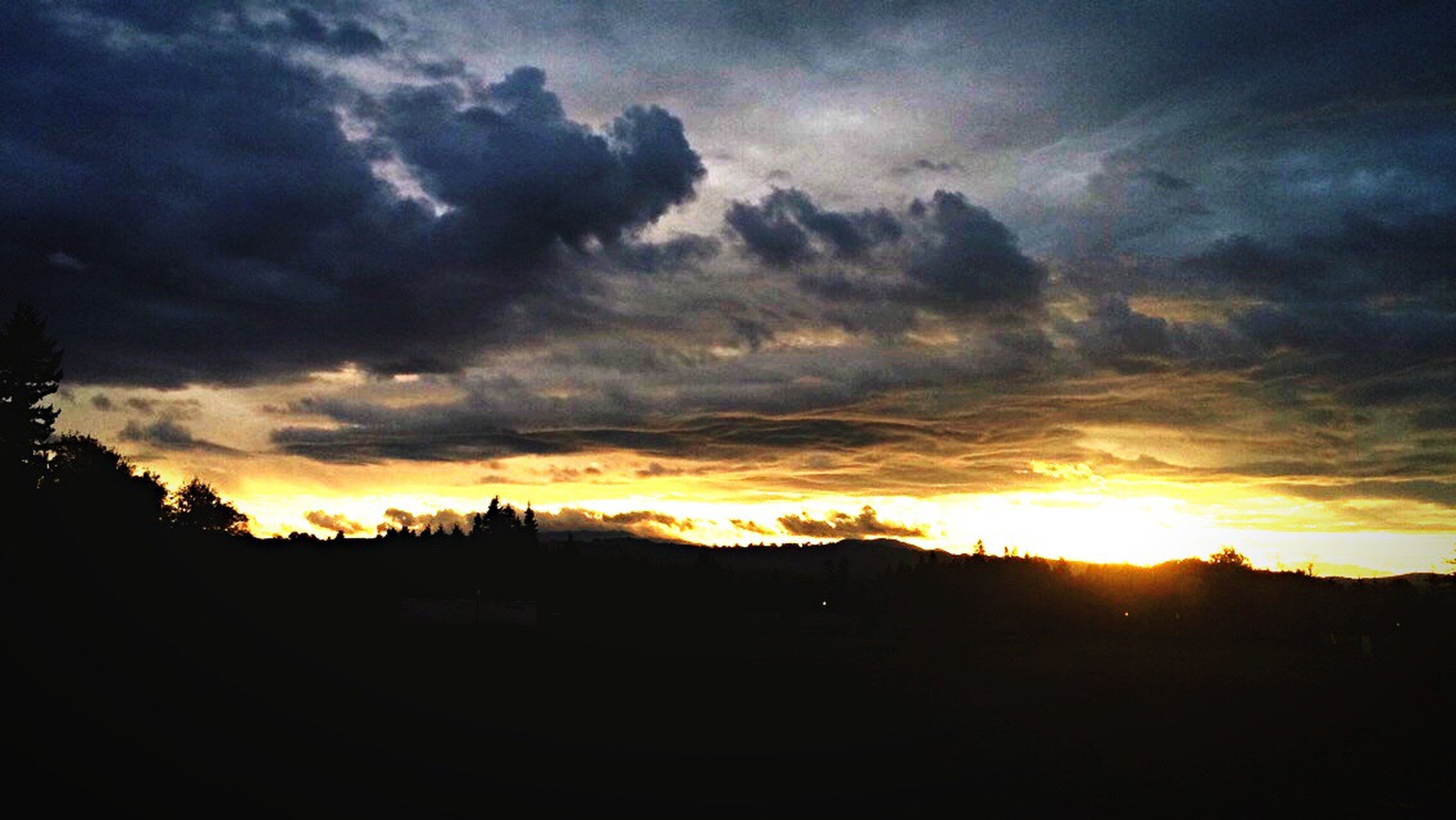 sunset, silhouette, sky, cloud - sky, orange color, scenics, beauty in nature, tranquil scene, dramatic sky, landscape, tranquility, cloudy, nature, sun, cloud, idyllic, dark, weather, field, moody sky