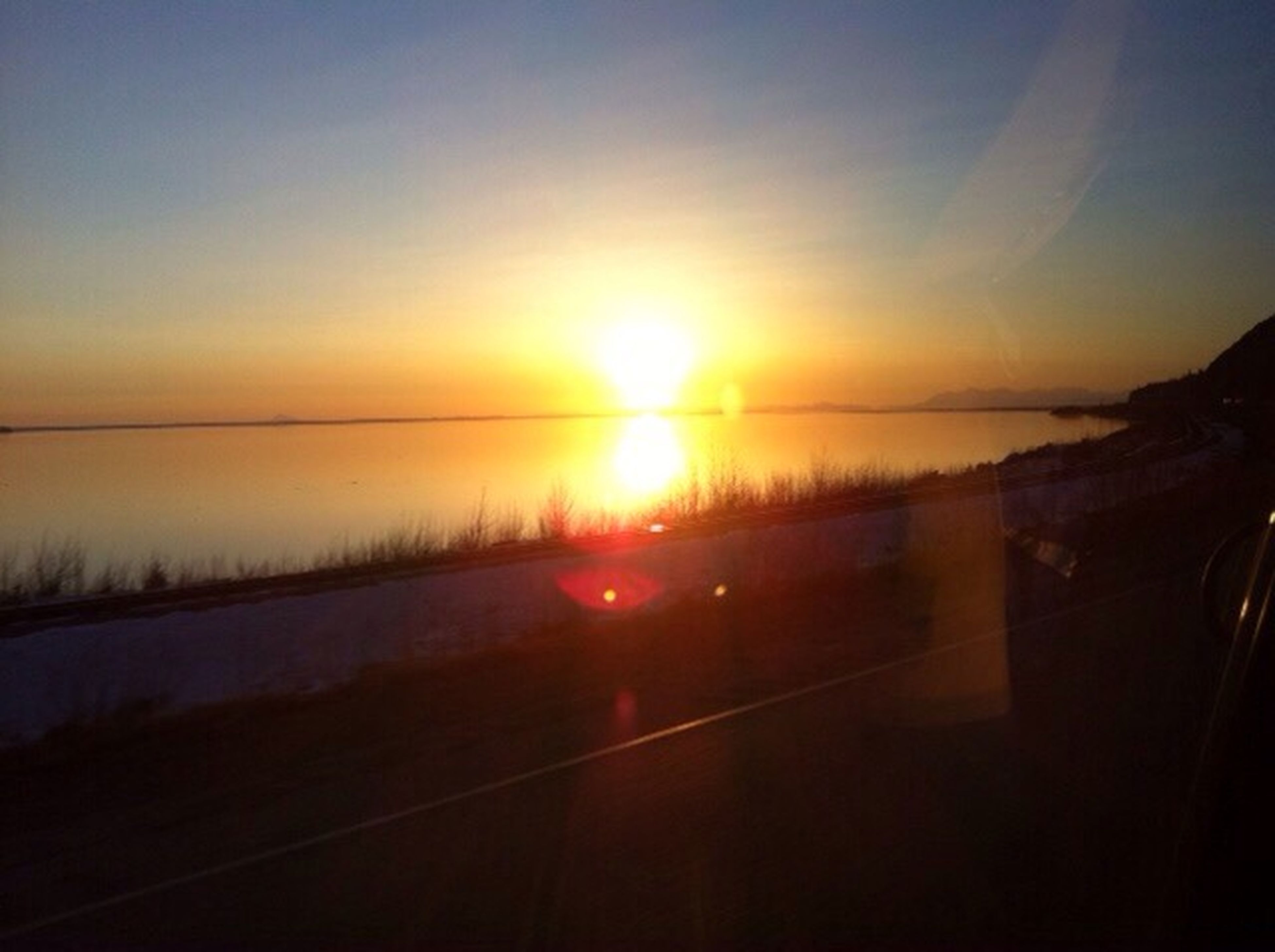 sunset, sun, transportation, sky, orange color, sunlight, scenics, tranquil scene, reflection, tranquility, road, beauty in nature, nature, sunbeam, silhouette, water, landscape, lens flare, glass - material, no people