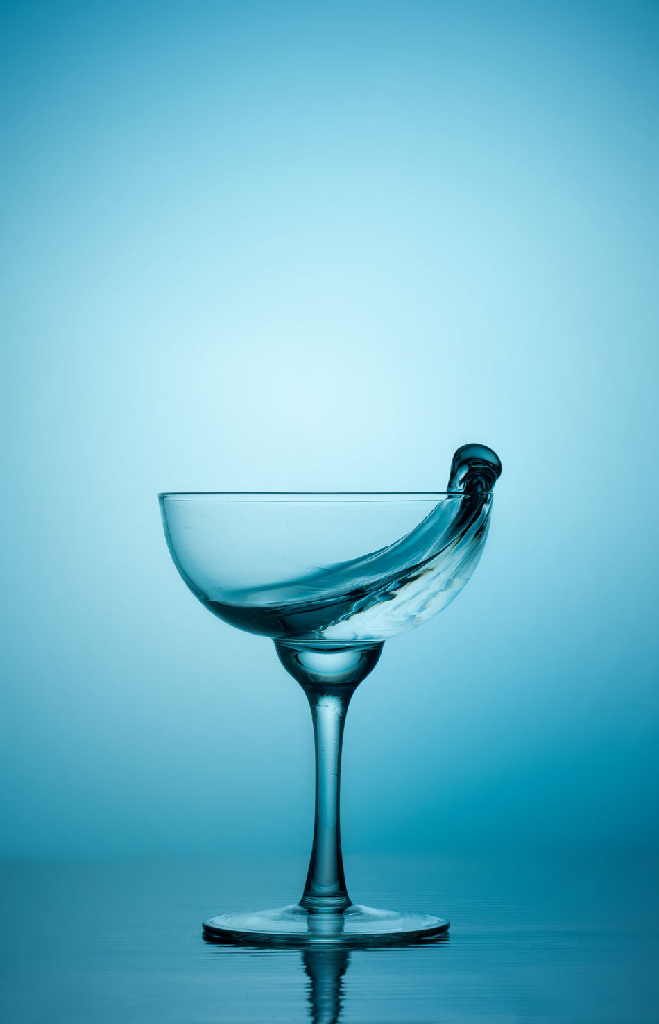 Water splash Alcohol Close-up Colored Background Day Drinking Glass Fragility Freshness Martini Glass No People Reflection Studio Shot Water