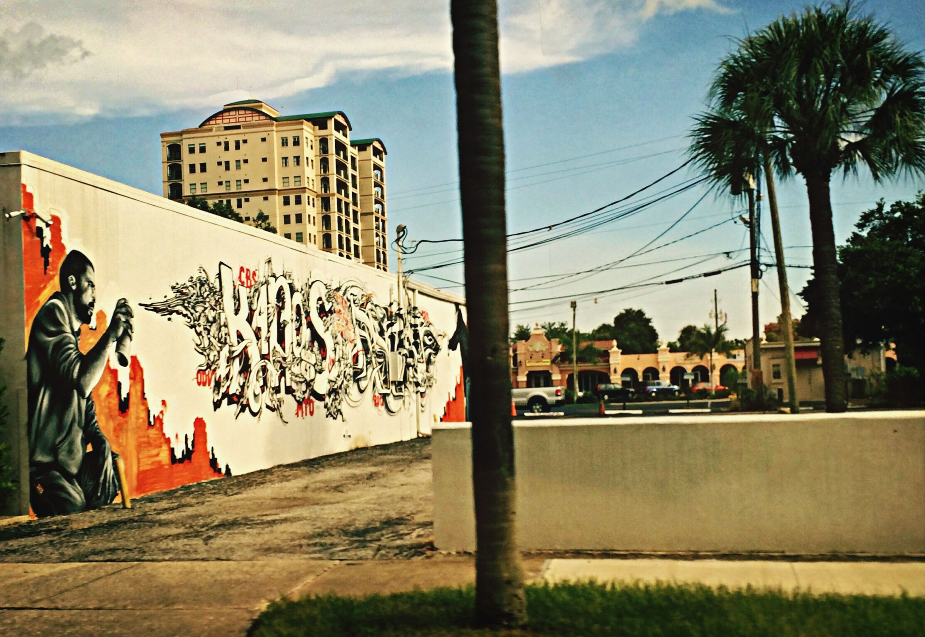 building exterior, architecture, built structure, sky, lifestyles, men, tree, palm tree, leisure activity, person, city, cloud - sky, graffiti, text, large group of people, street, day, cloud, outdoors