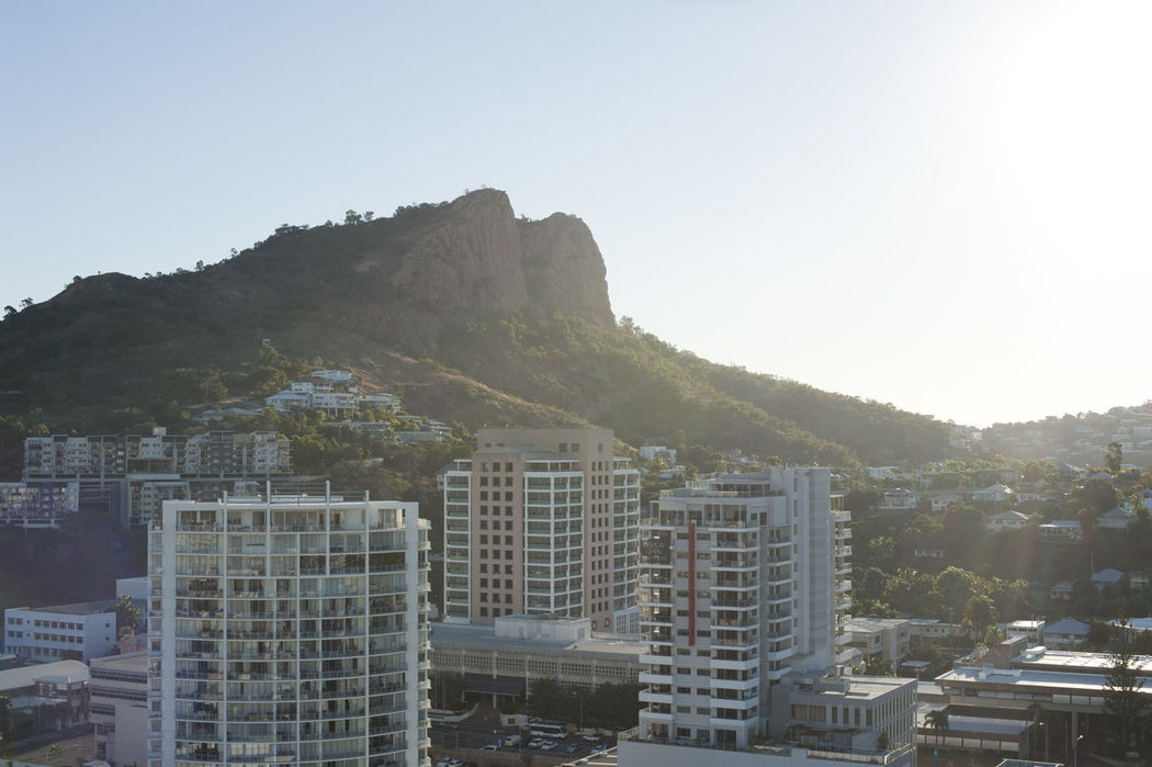 View of modern high-rise buildings in Townsville, Queensland overlooked by a mountain peak backlit by a hot summer sun in a travel concept Architecture Bright Building Exterior Built Structure City City Cityscape Clear Sky Day Flare Mountain No People Outdoors Queensland Queensland Australia Sky Sun Townsville Townsville, Queensland.