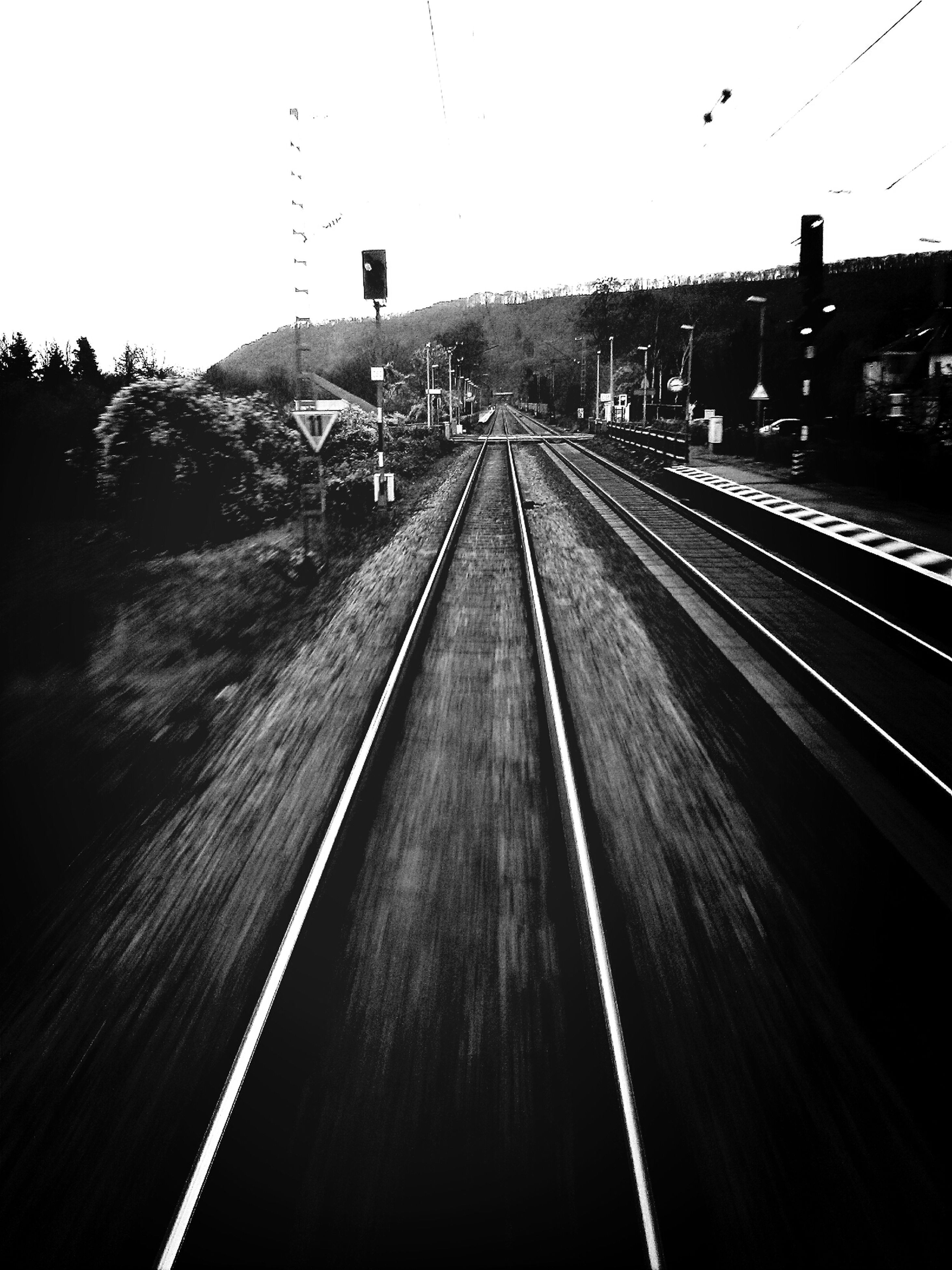 railroad track, transportation, rail transportation, public transportation, railroad station platform, railroad station, the way forward, clear sky, diminishing perspective, vanishing point, mode of transport, railway track, travel, built structure, train - vehicle, on the move, high angle view, journey, sky, outdoors