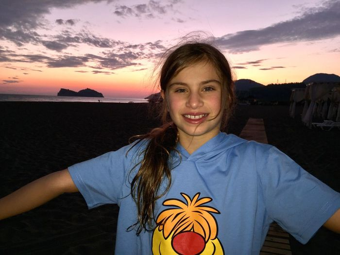 Sunset Looking At Camera Portrait Real People Waist Up One Person Smiling Lifestyles Leisure Activity Sky Cloud - Sky Outdoors Young Women Beautiful Girl Beauty In Nature Adolescent Beach Vacations Fill In Flash