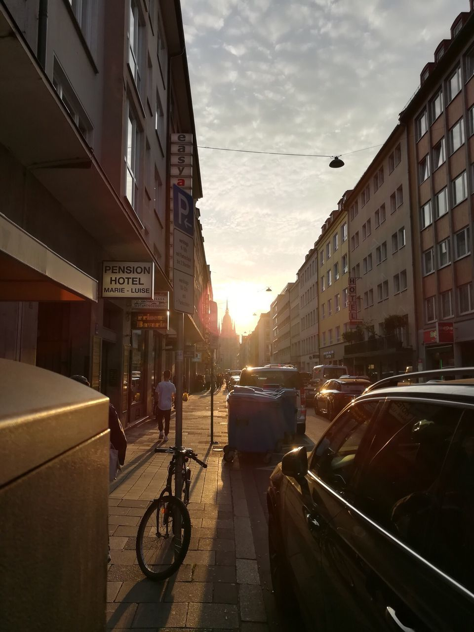 building exterior, architecture, car, city, built structure, transportation, land vehicle, street, mode of transport, sky, city life, outdoors, sunlight, road, sunset, day, no people
