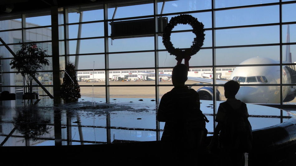 Airport Terminal Boys Christmas Christmas Garland City City Life Coming Home For Christmas Detroit Airport Fountain Glass Glass - Material Indoors  Leisure Activity Lifestyles Looking Through Window Men Person Plane Silhouette Sky Standing The Culture Of The Holidays Transparent Waiting For The Flight Window