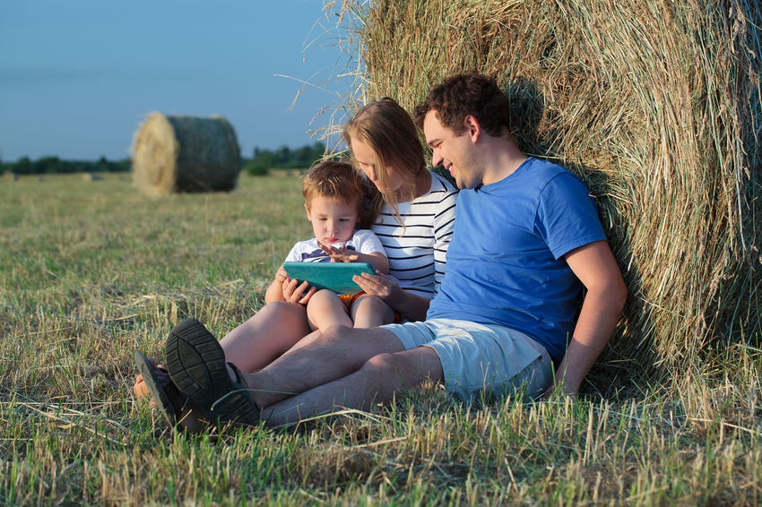 Bale  Boy Caucasian Computer Dad Family Father Field Hay Mother Outdoors Pad Parent Parenthood Play Roll Rural Son TAB Touch Pad Touchpad