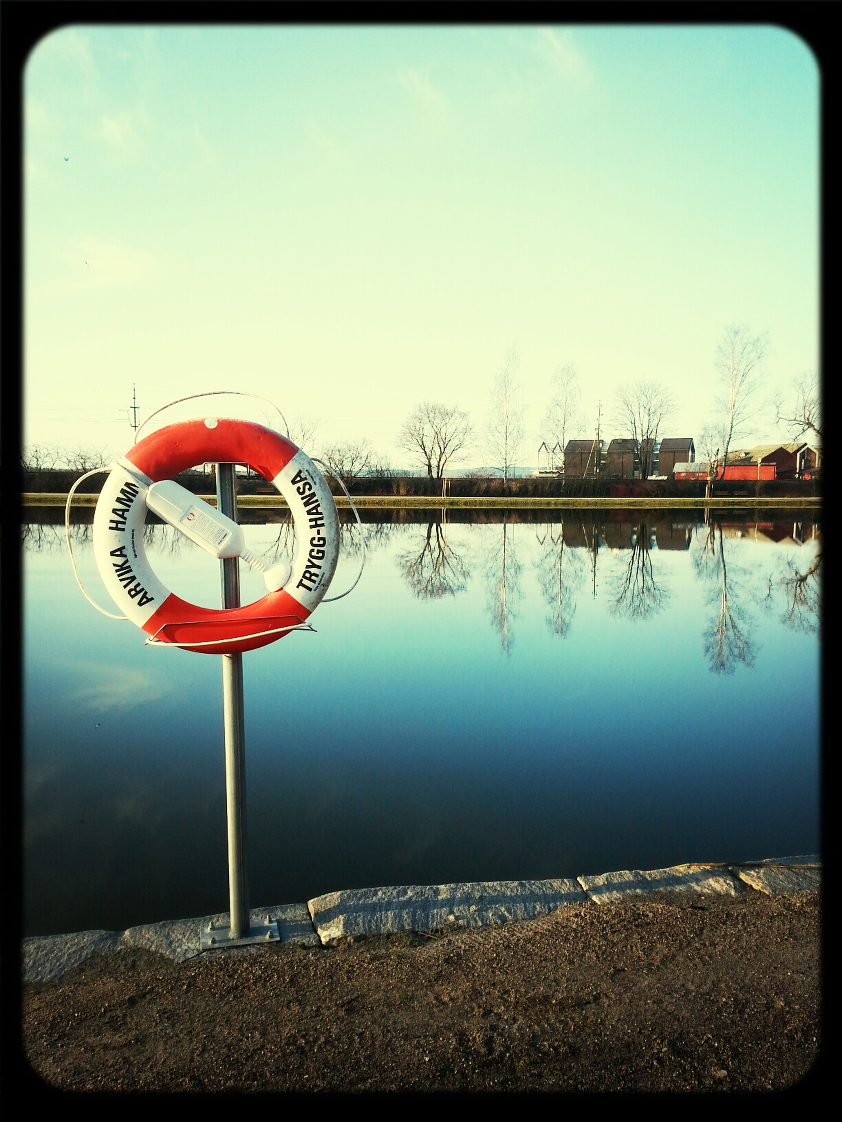 transfer print, auto post production filter, clear sky, water, red, sky, blue, circle, reflection, outdoors, day, transportation, tree, no people, copy space, river, protection, tranquility, lake, nature