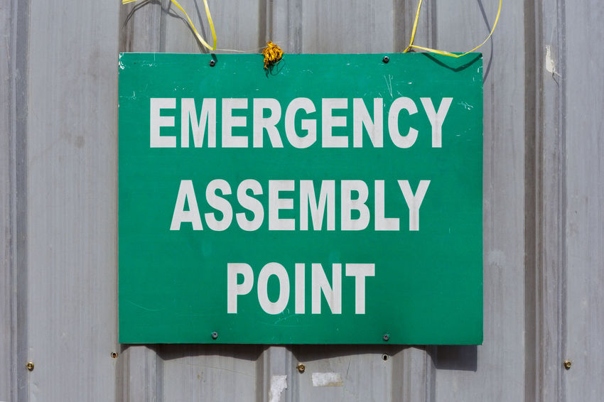 Green Emergency Assembly Point sign mounted to a metal construction site fence. Emergency Hanging Sign Assembly Point Building Exterior Built Structure Close-up Communication Day Green Color Health And Safety No People Outdoors Text Warning Sign
