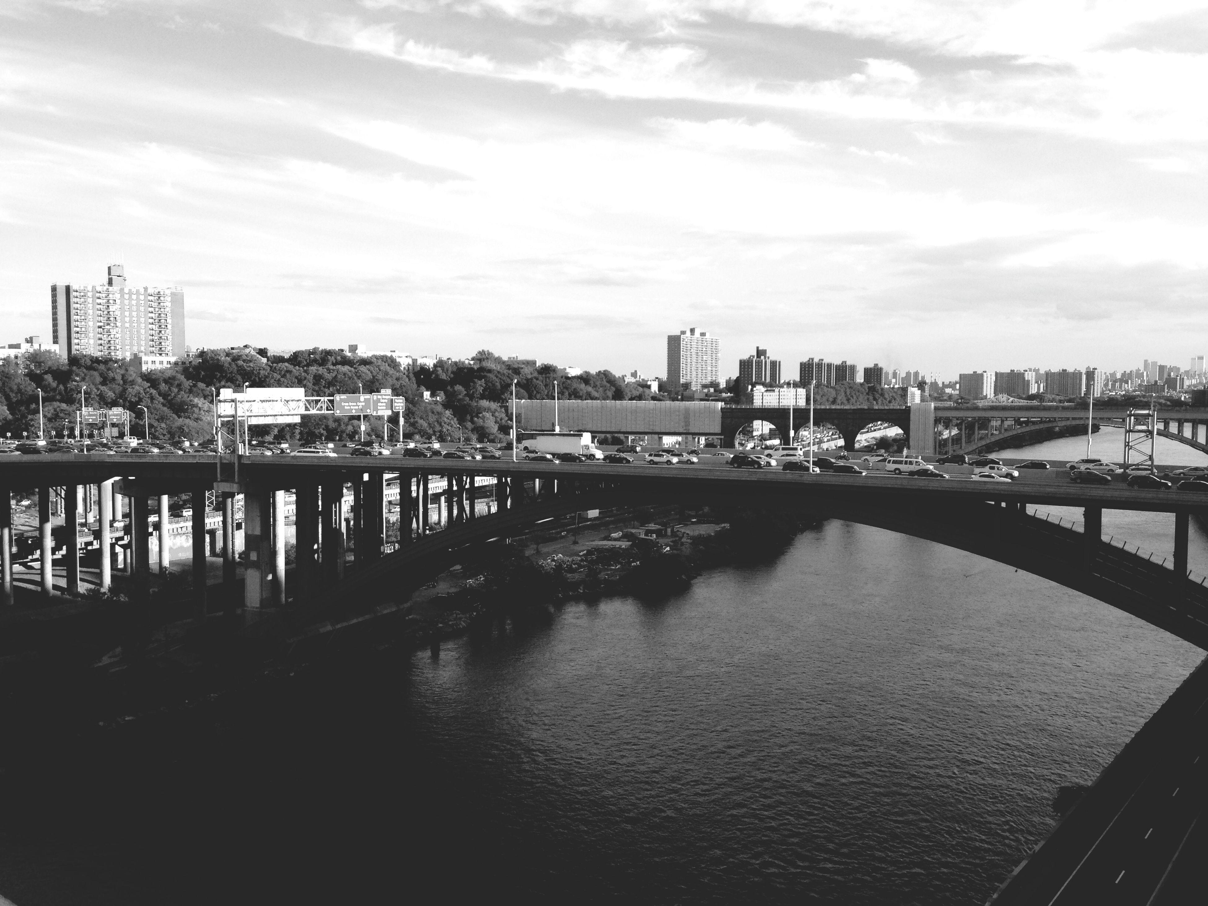 architecture, built structure, building exterior, city, water, river, bridge - man made structure, sky, connection, cityscape, waterfront, cloud - sky, transportation, bridge, cloud, railing, city life, engineering, outdoors, skyscraper
