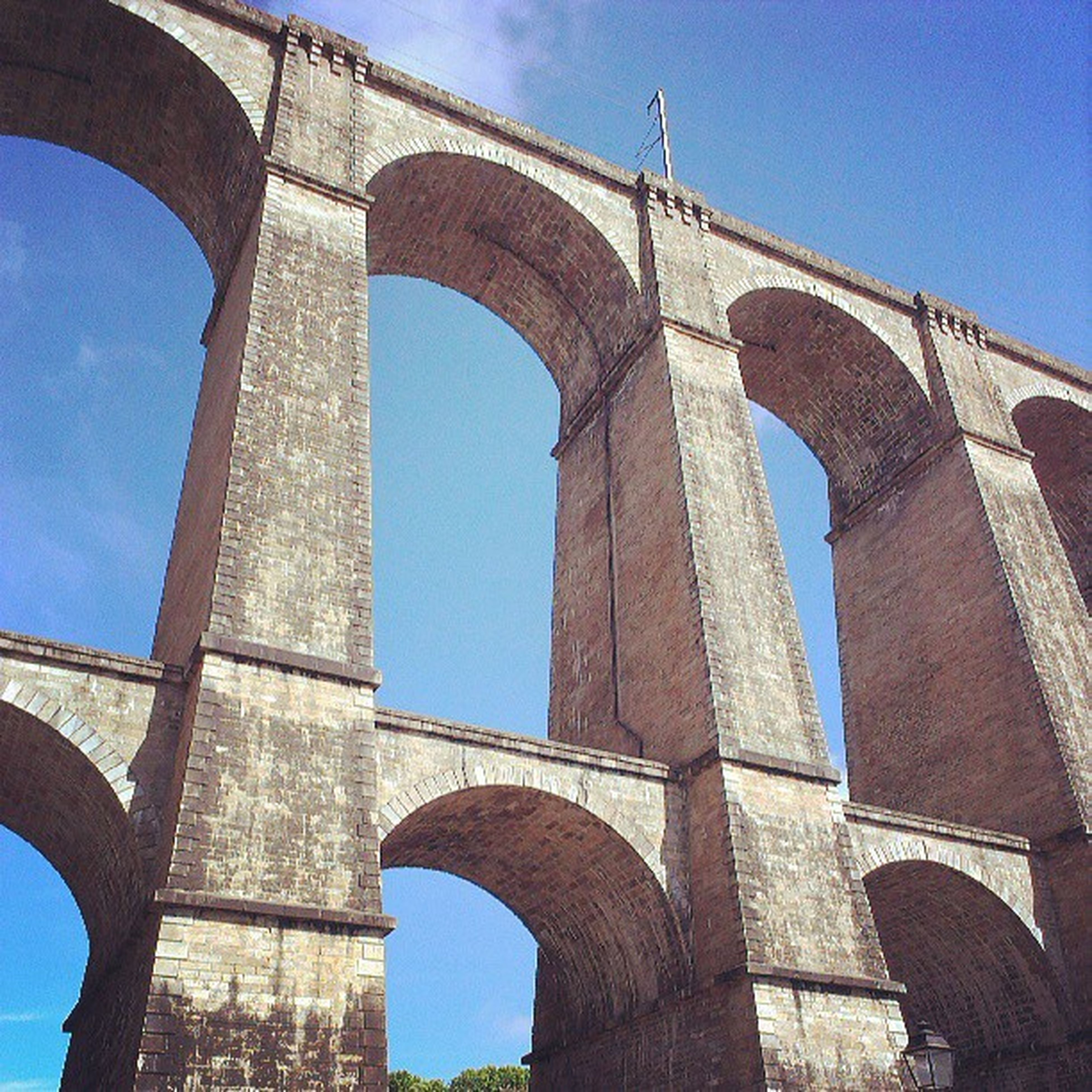 architecture, built structure, low angle view, arch, connection, bridge - man made structure, history, engineering, clear sky, international landmark, famous place, bridge, architectural column, travel destinations, blue, sky, column, travel, building exterior, tourism