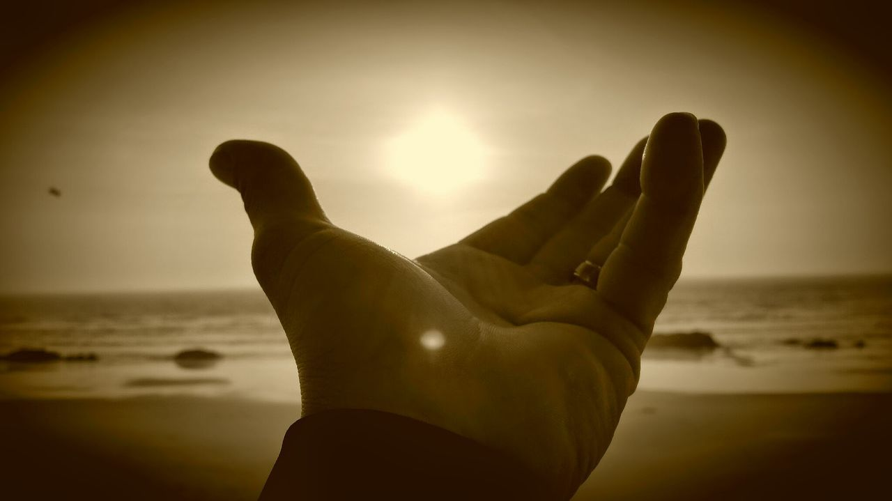 beach, sea, sun, sunset, silhouette, human hand, horizon over water, shore, sand, one person, human body part, water, outdoors, real people, sky, nature, beauty in nature, close-up, vacations, day, people