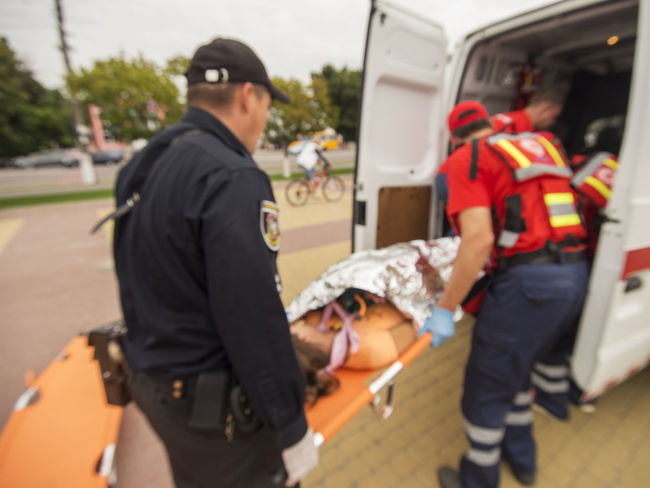 Unfocused photo. Employees of the Red Cross and the police evacuate the wounded during the terrorist attack on the ambulance. Reconstruction. Ambulance Casual Clothing Day Employees Evacuate Focus On Foreground Food And Drink Holding Leisure Activity Lifestyles Person Photo Police Red Cross Standing Street Terrorist Attack Unfocused Wounded