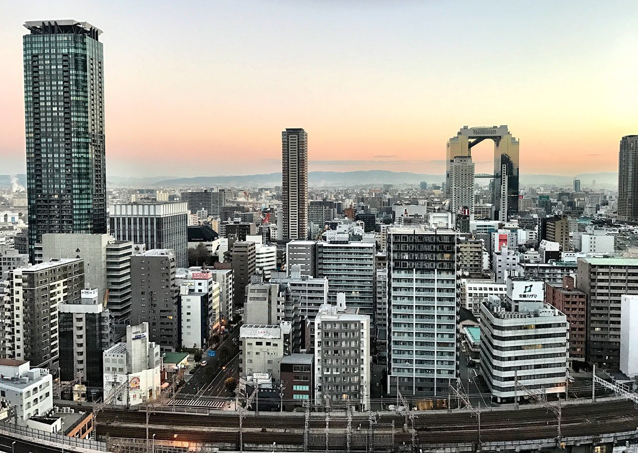 skyscraper, architecture, cityscape, building exterior, city, modern, sunset, skyline, tower, built structure, travel destinations, tall, urban skyline, development, financial district, downtown district, sky, outdoors, no people, downtown, clear sky, growth, water, office park, day
